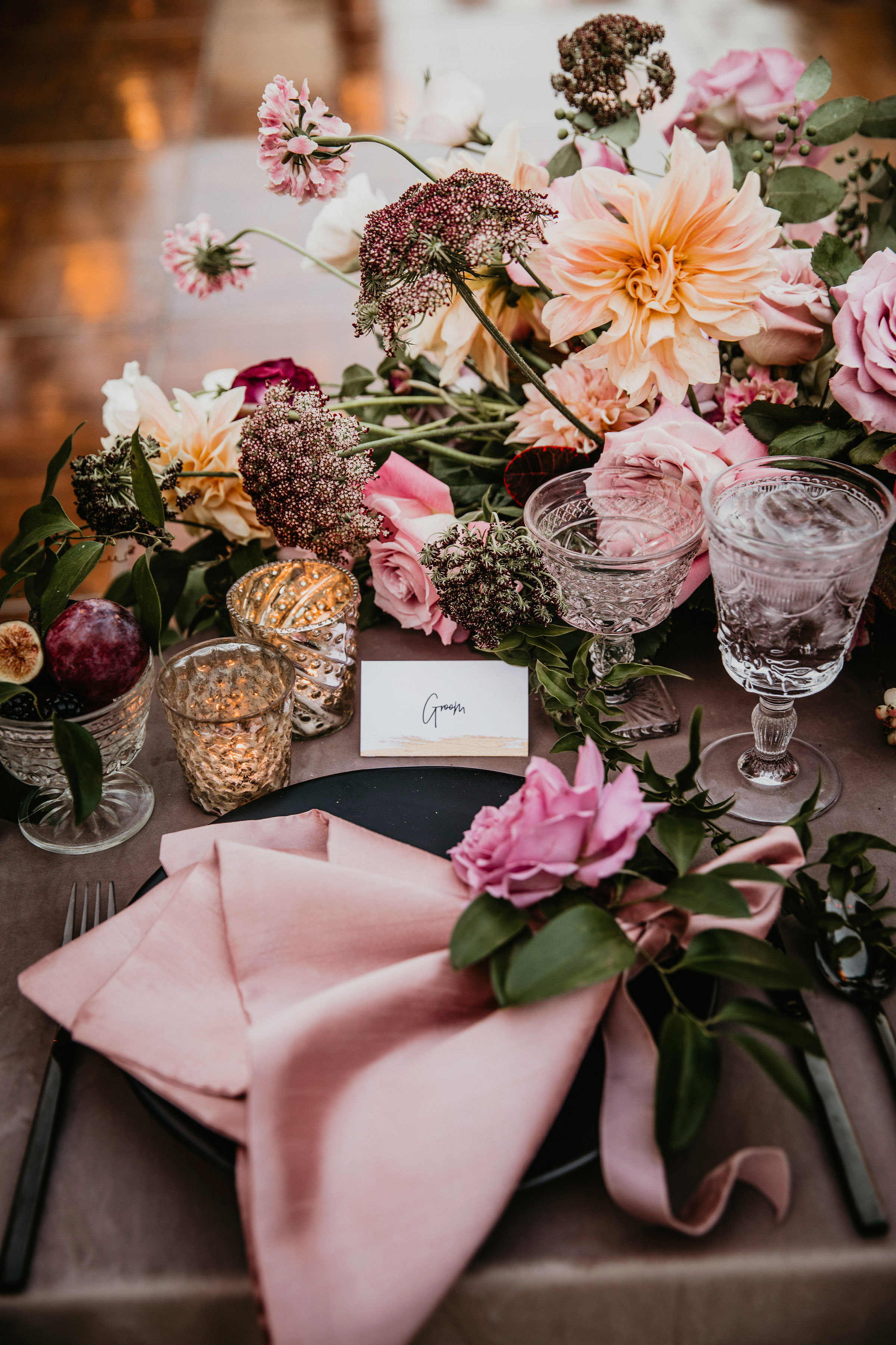table place setting with gray velvet linen black chargers and pink napkins