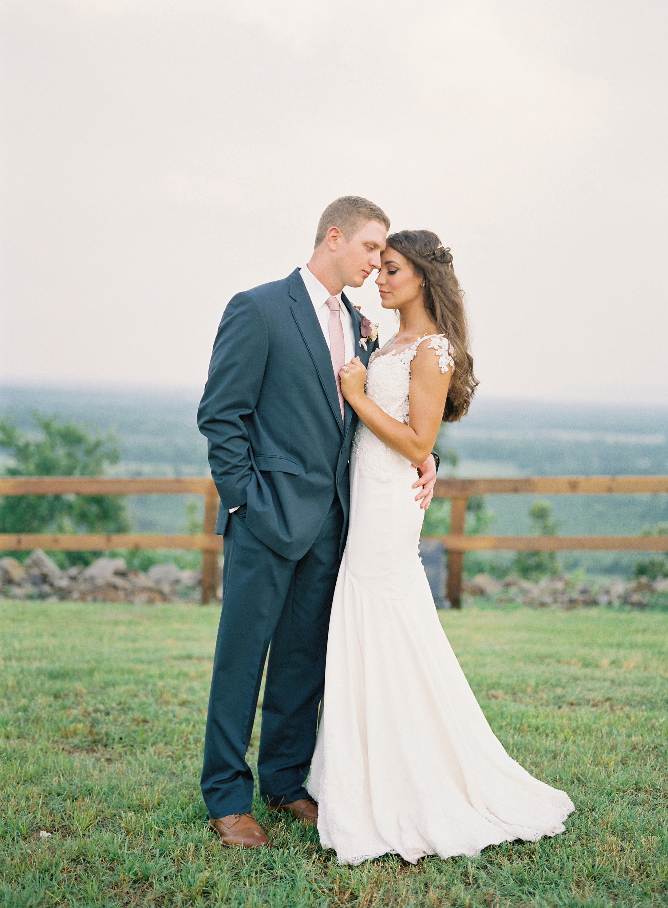 wedding couple pose outdoors river valley view fence