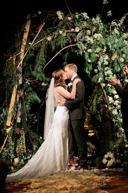 wedding bride groom kiss below greenery white flower arch