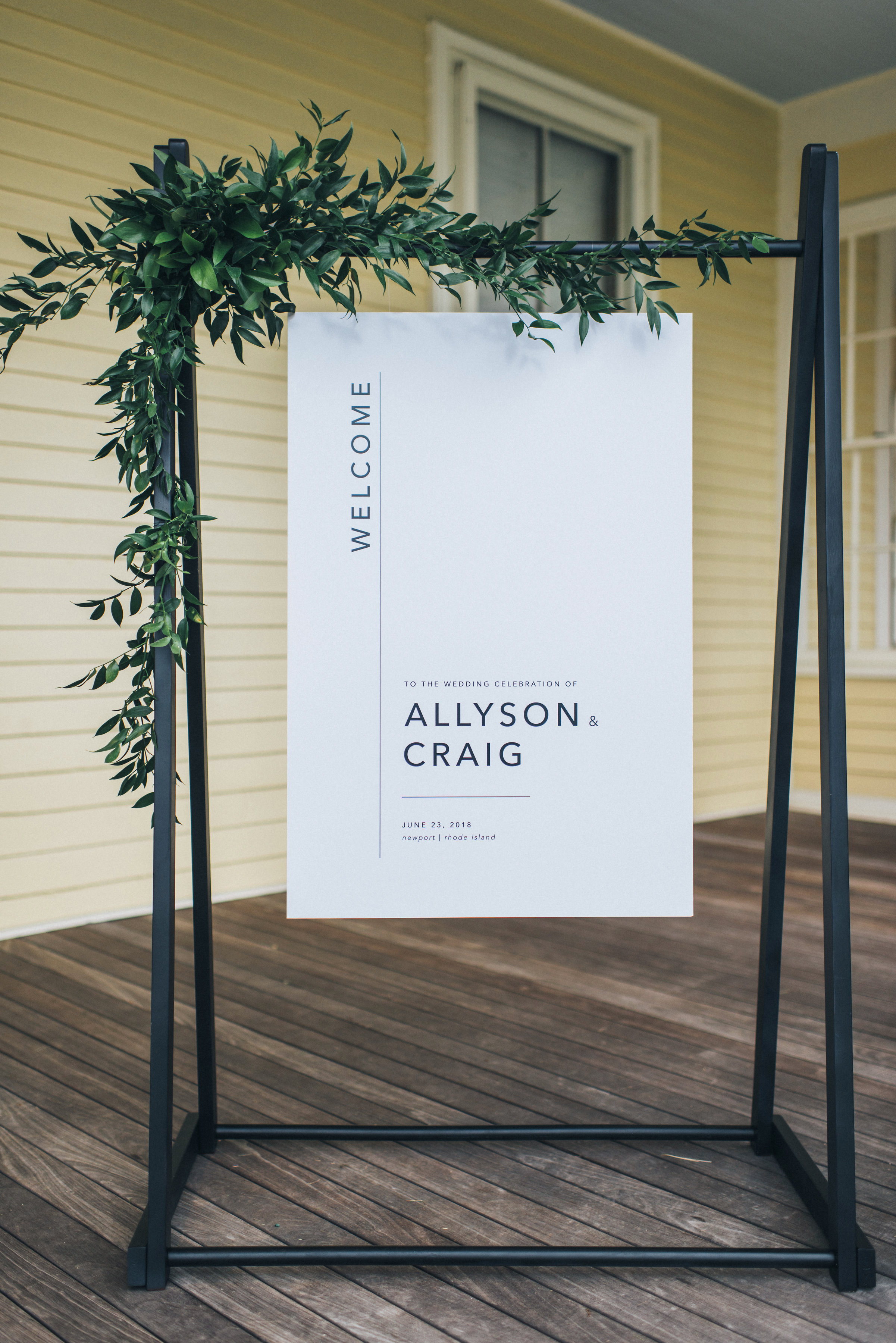 wedding welcome sign on deck with greenery