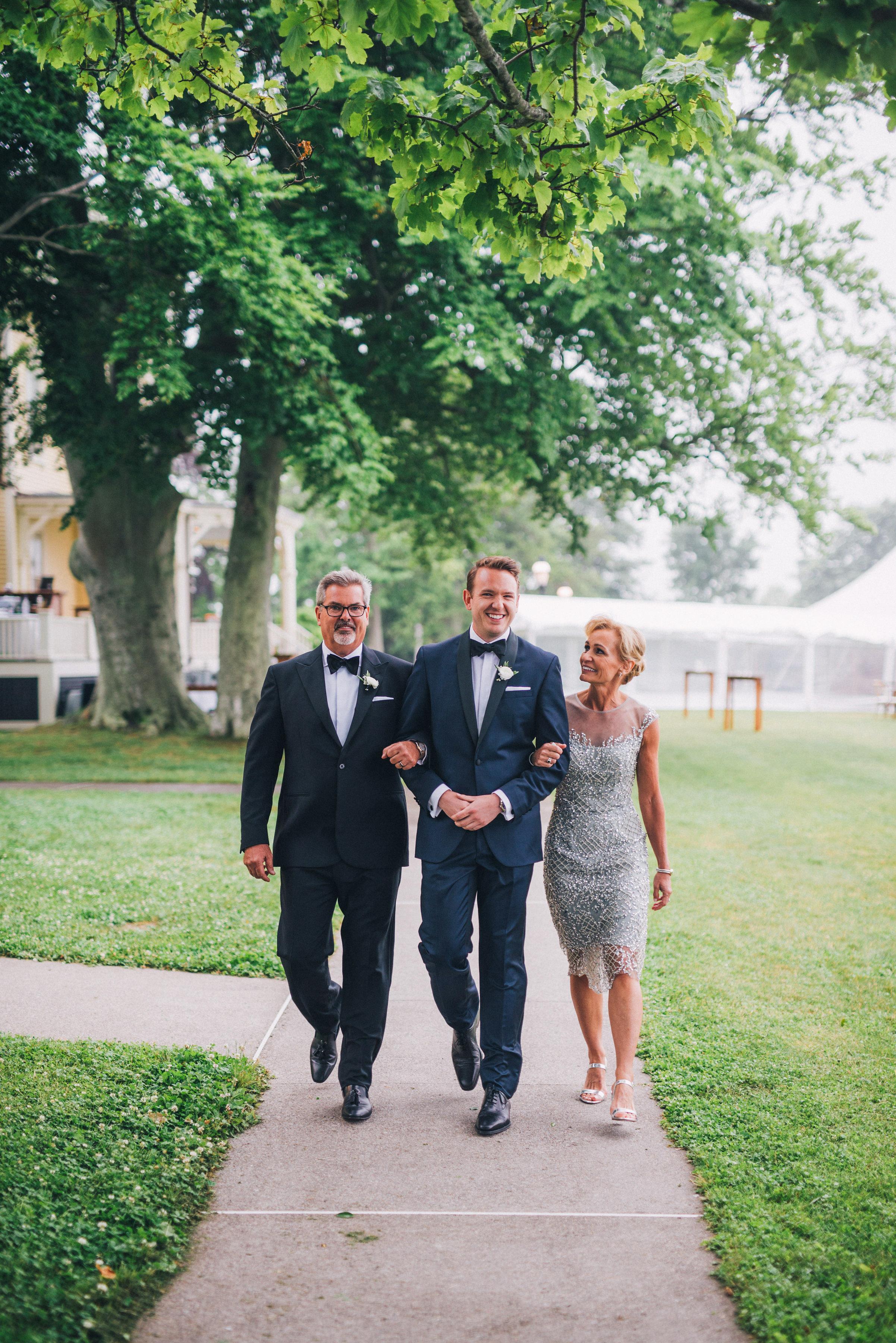 groom escorting parents up sidewalk