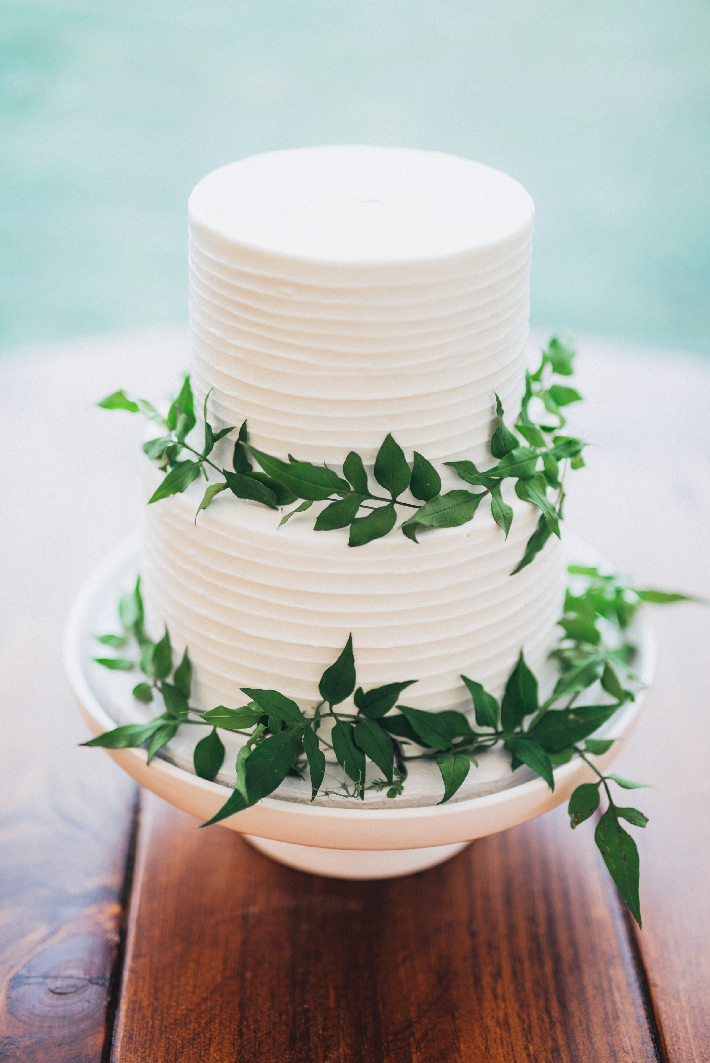 layered white wedding cake with greenery