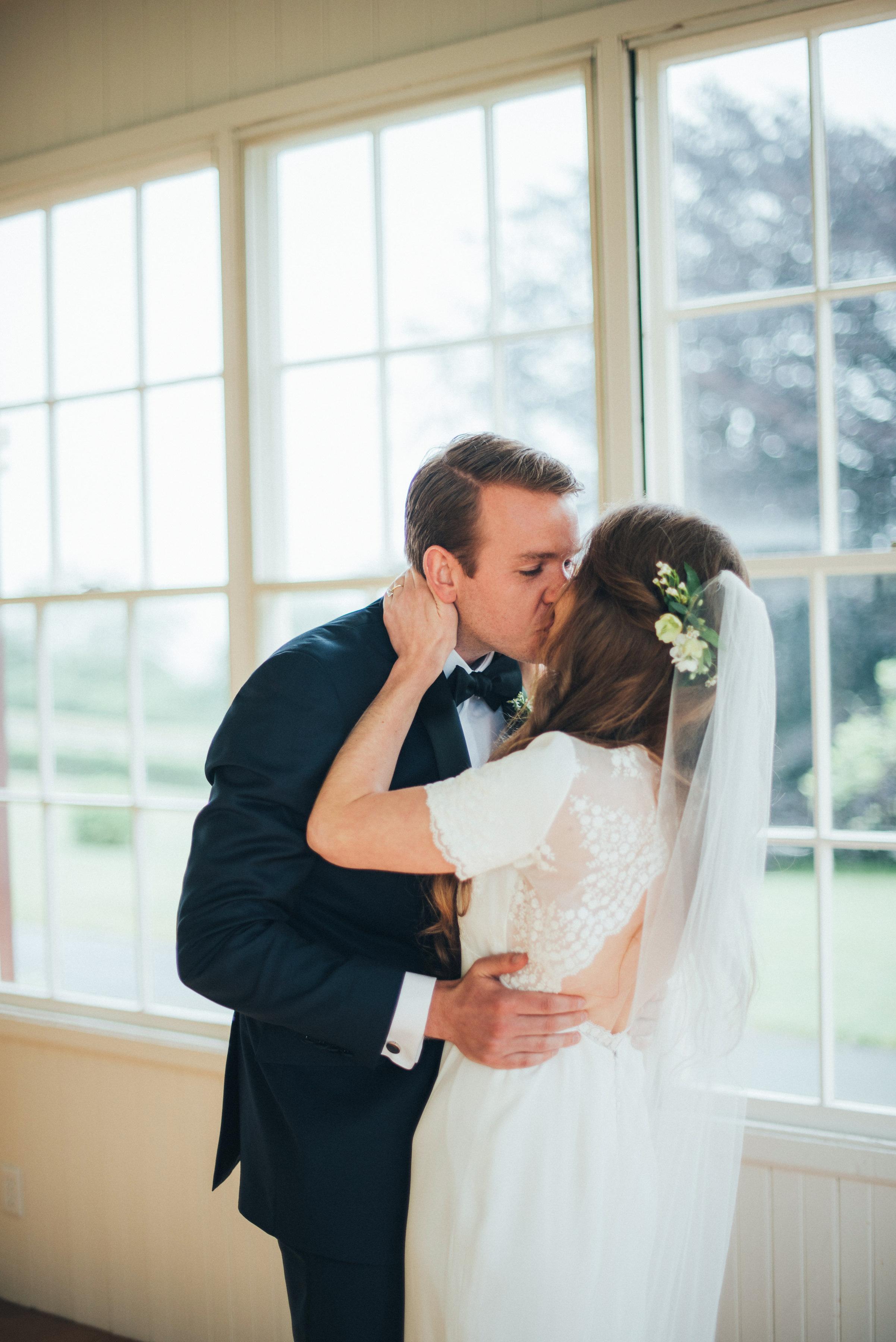 bride groom kiss in front of windows