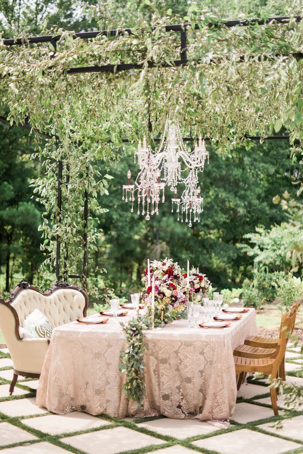 lace table setting beneath greenery and crystal chandelier