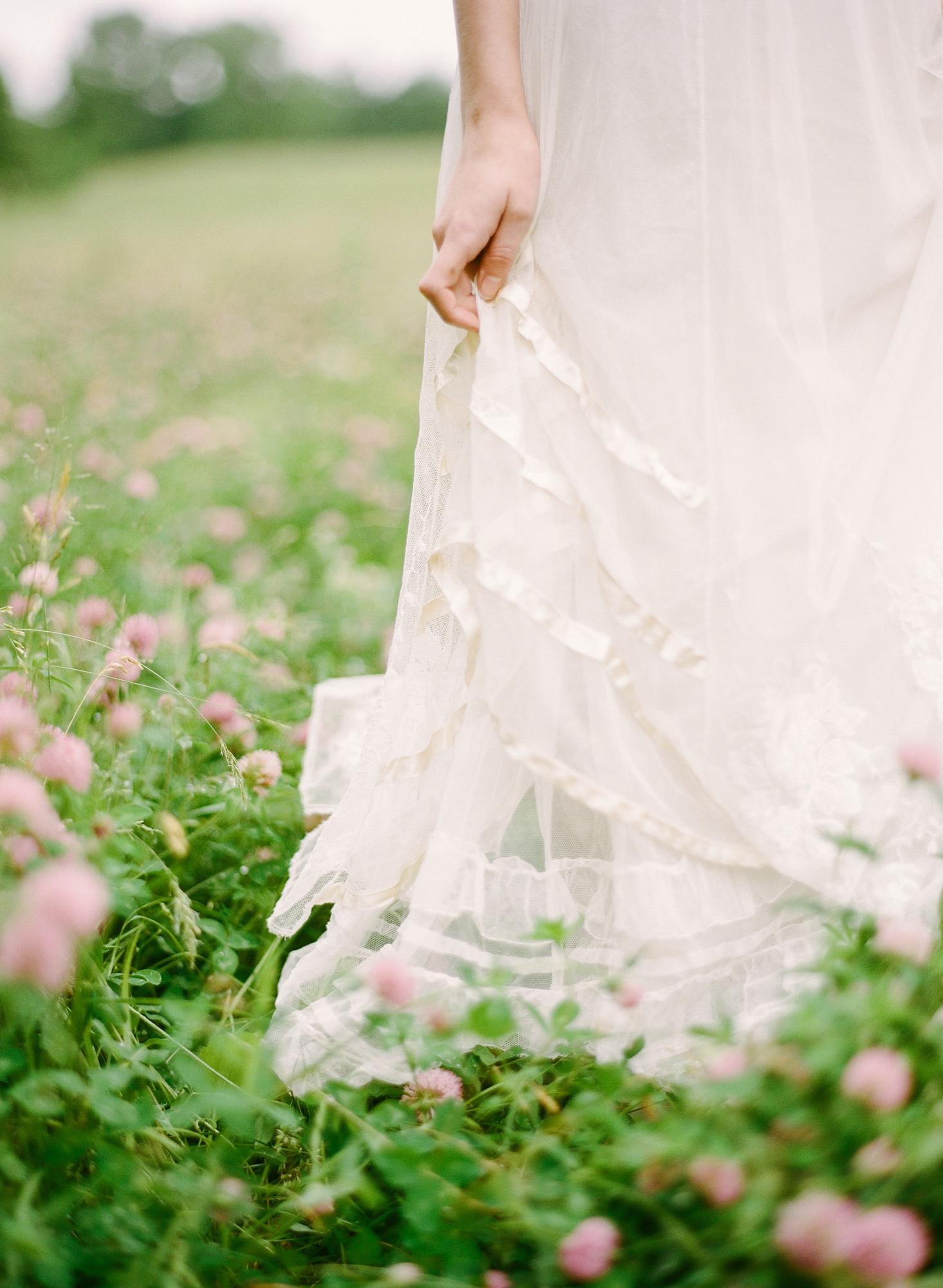 bride wearing petticoat standing in field of wildflowers