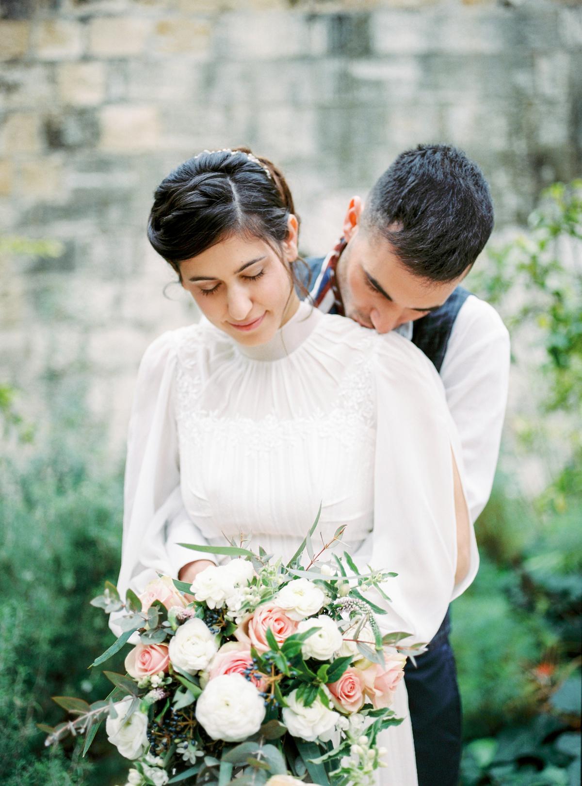 groom kissing shoulder of bride wearing high-neck wedding dress