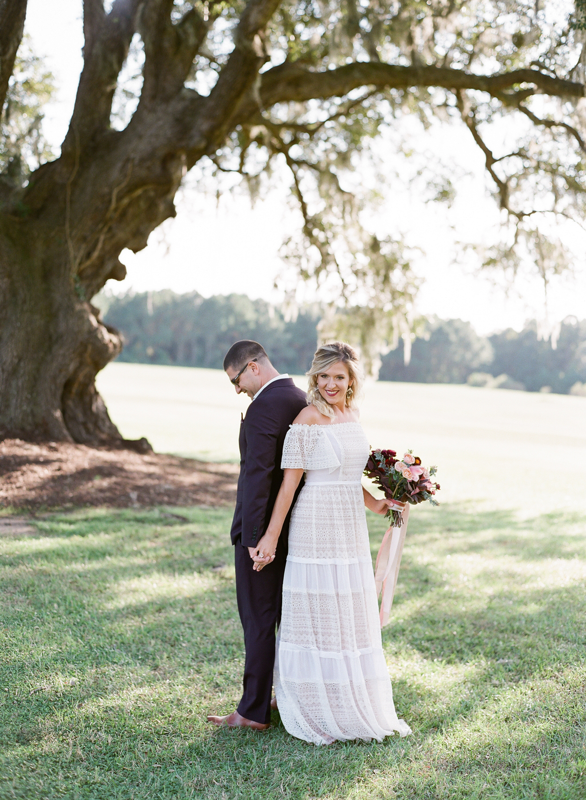 Couple stands back to back under tree for first look