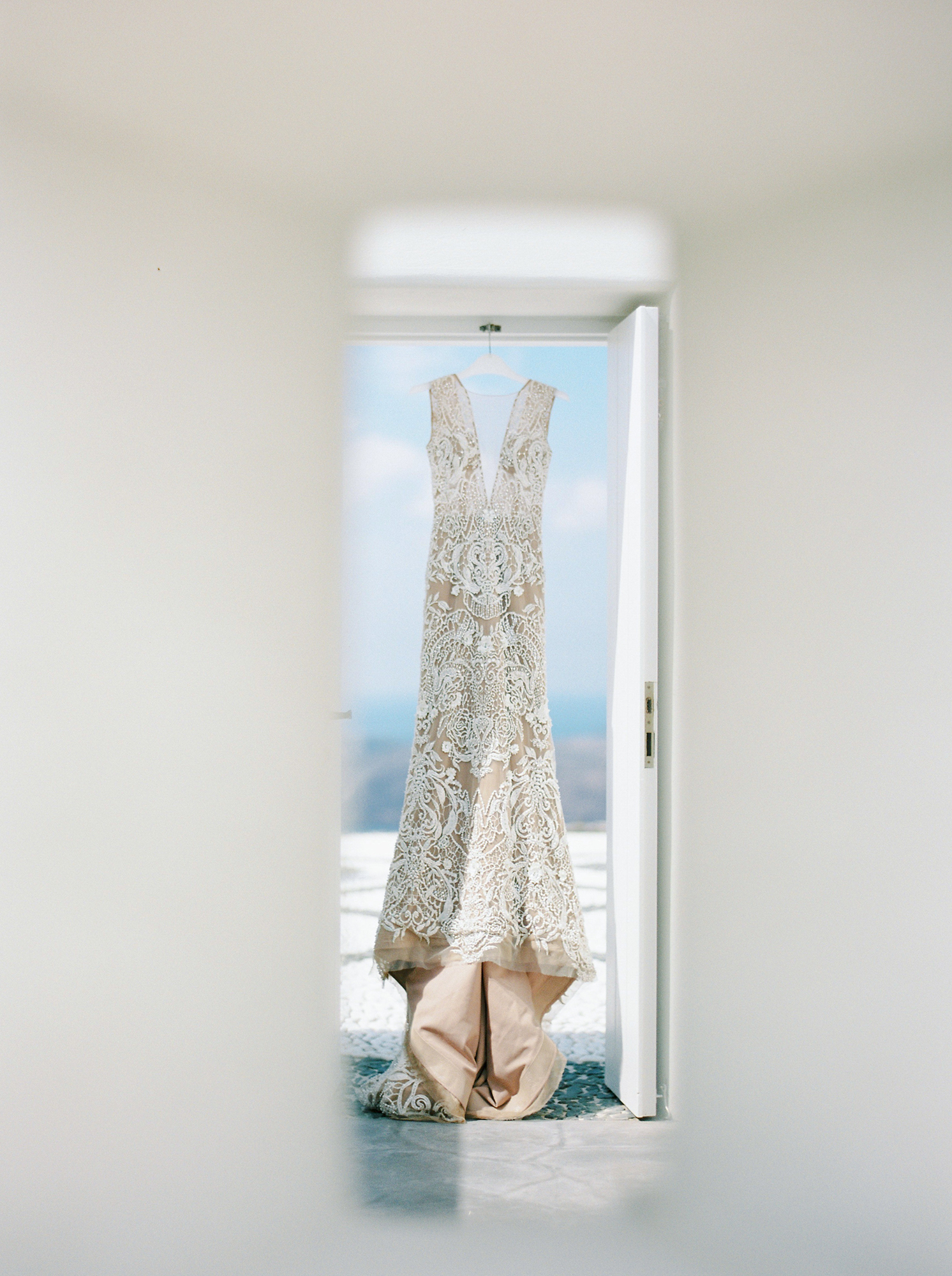 angie prayogo wedding bride wedding dress hanging in doorway