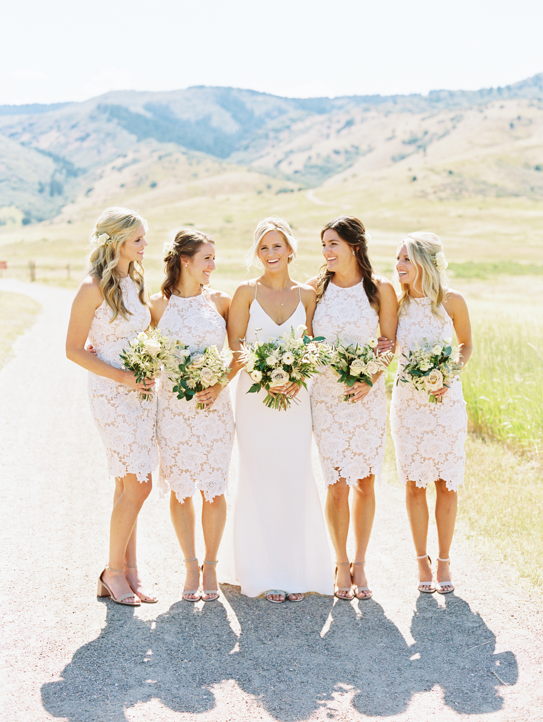 bride surrounded by bridesmaids outside