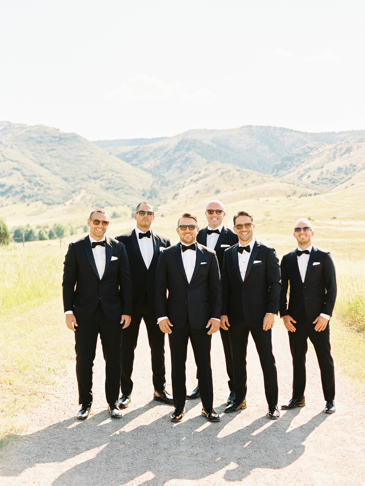 groom stands with groomsmen wearing classic black tuxedos