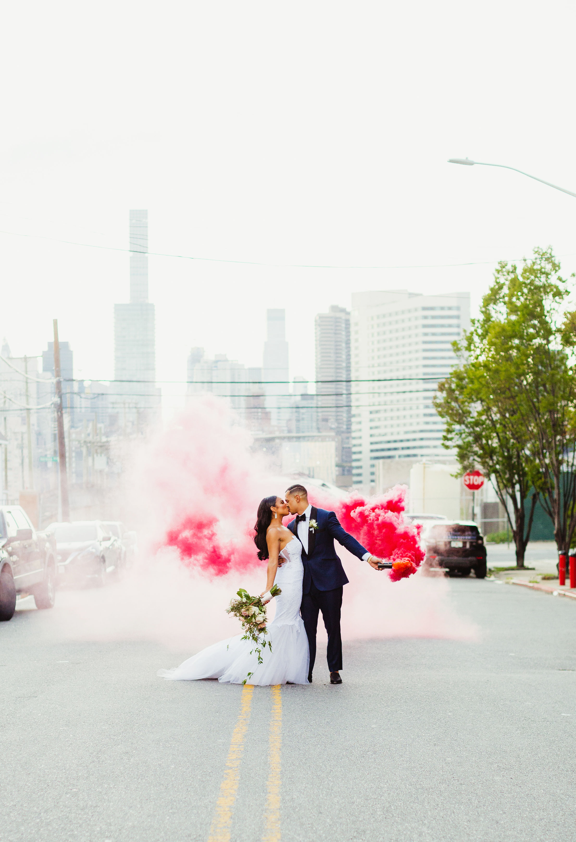 couple kissing with pink smokebomb