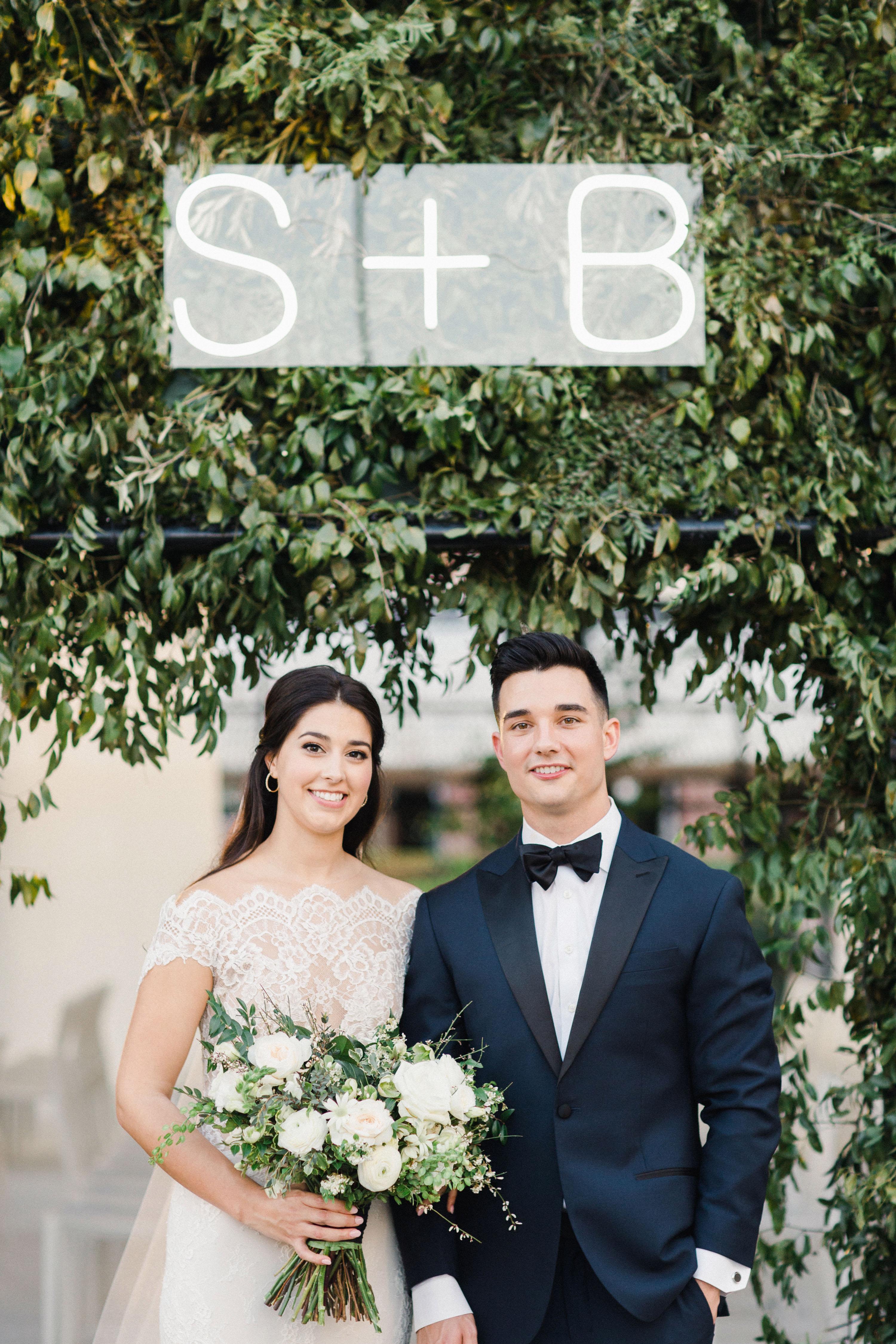 bride groom posing under initials neon sign