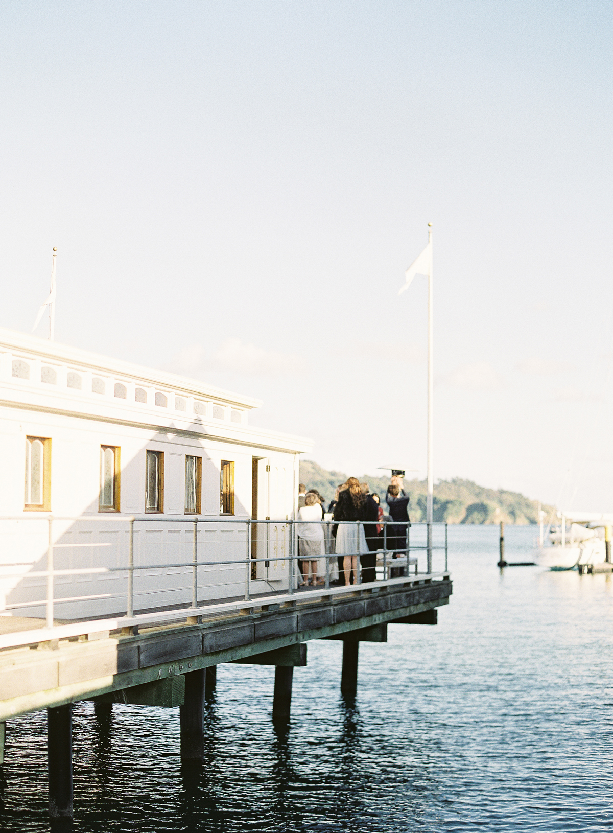 guests gather on deck over water for cocktail hour