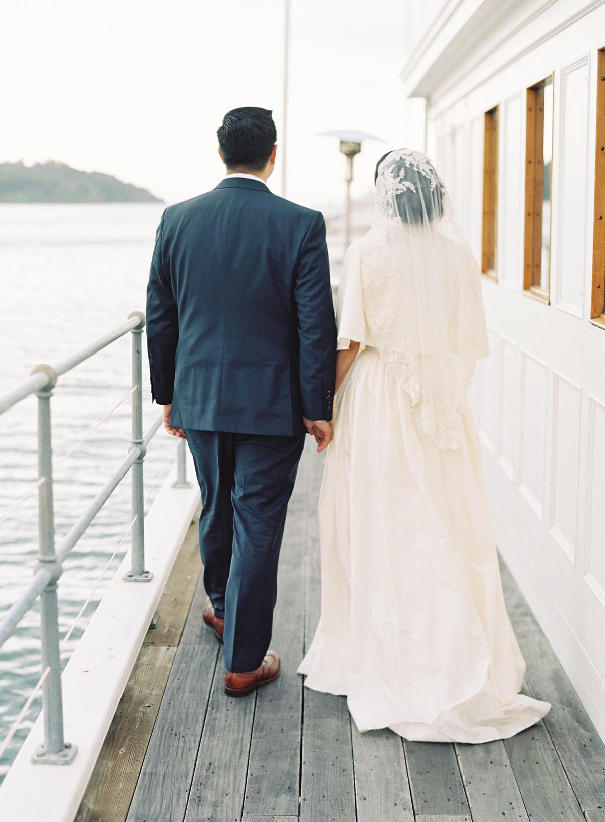 bride and groom walking away next to water