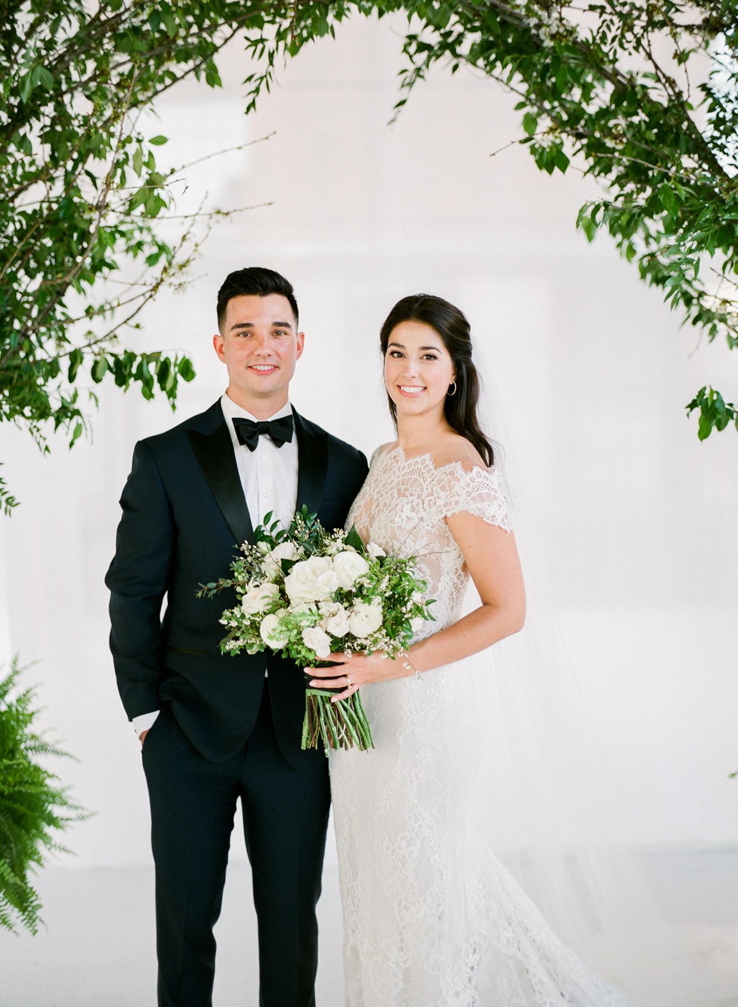 wedding bride groom pose under greenery arch