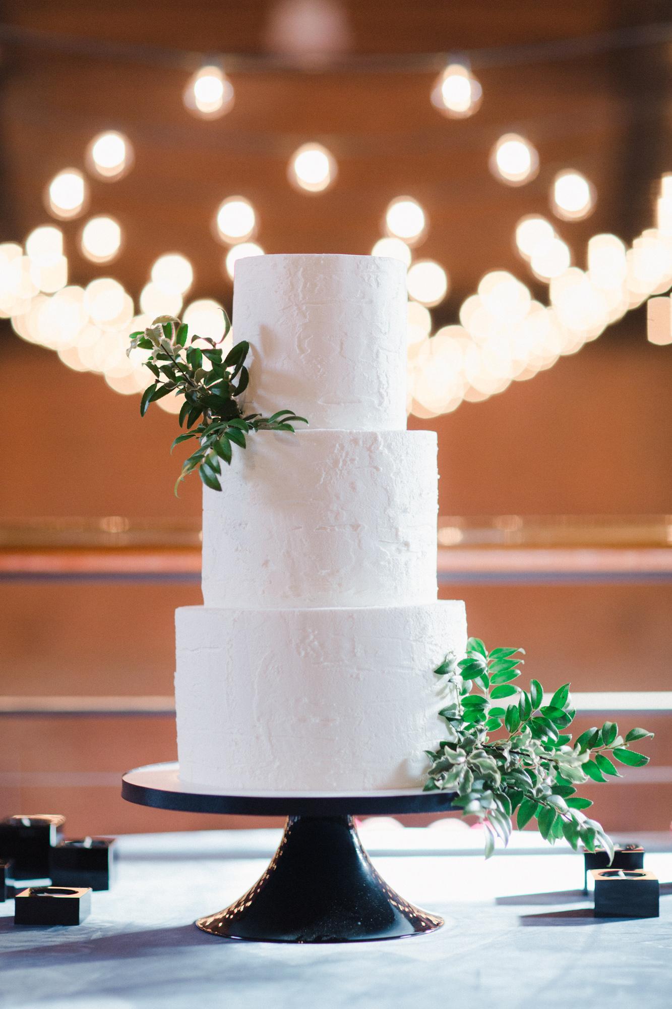 white wedding three tier cake with greenery
