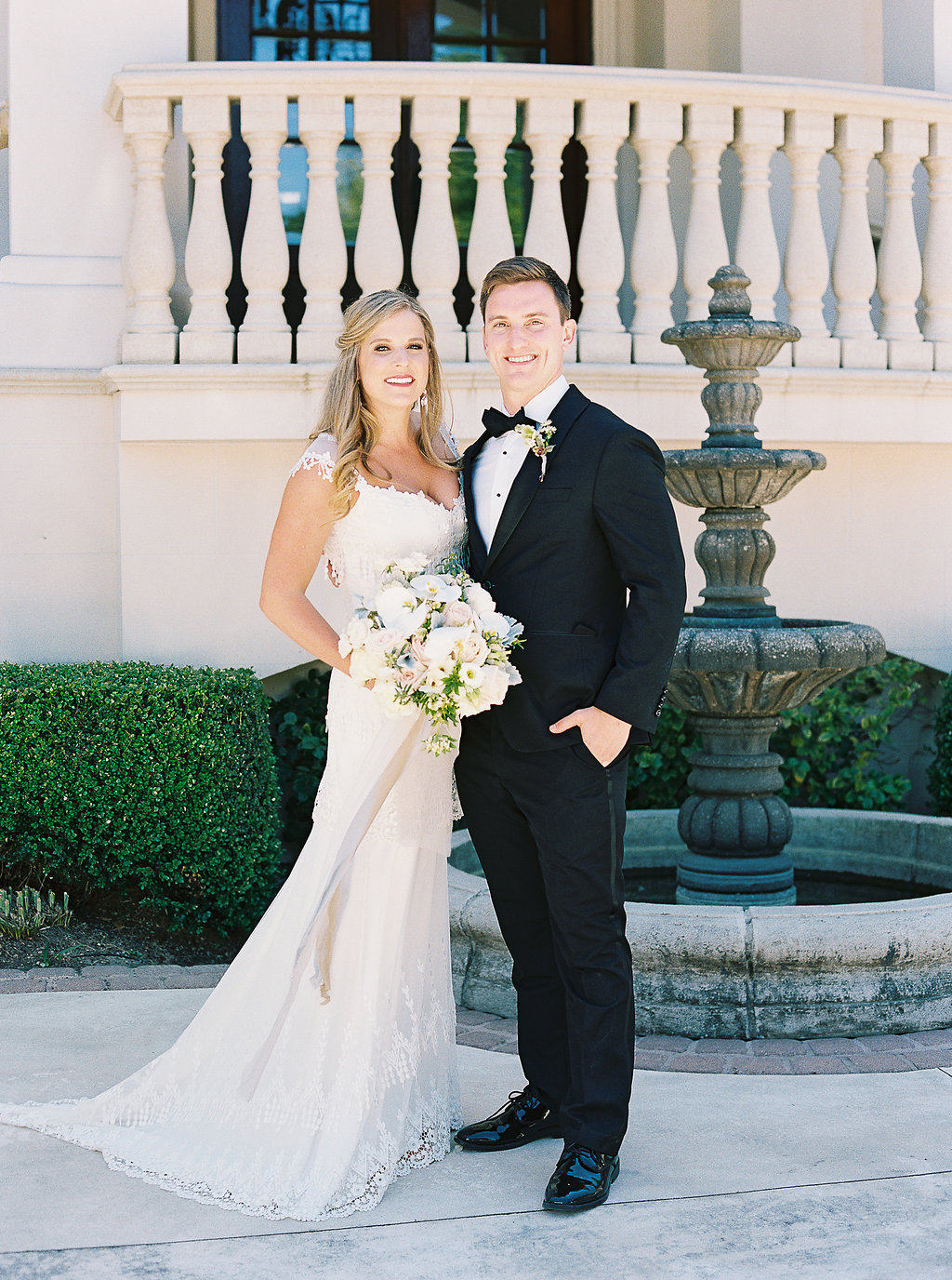 bride and groom posing in front of fountain outside of venue