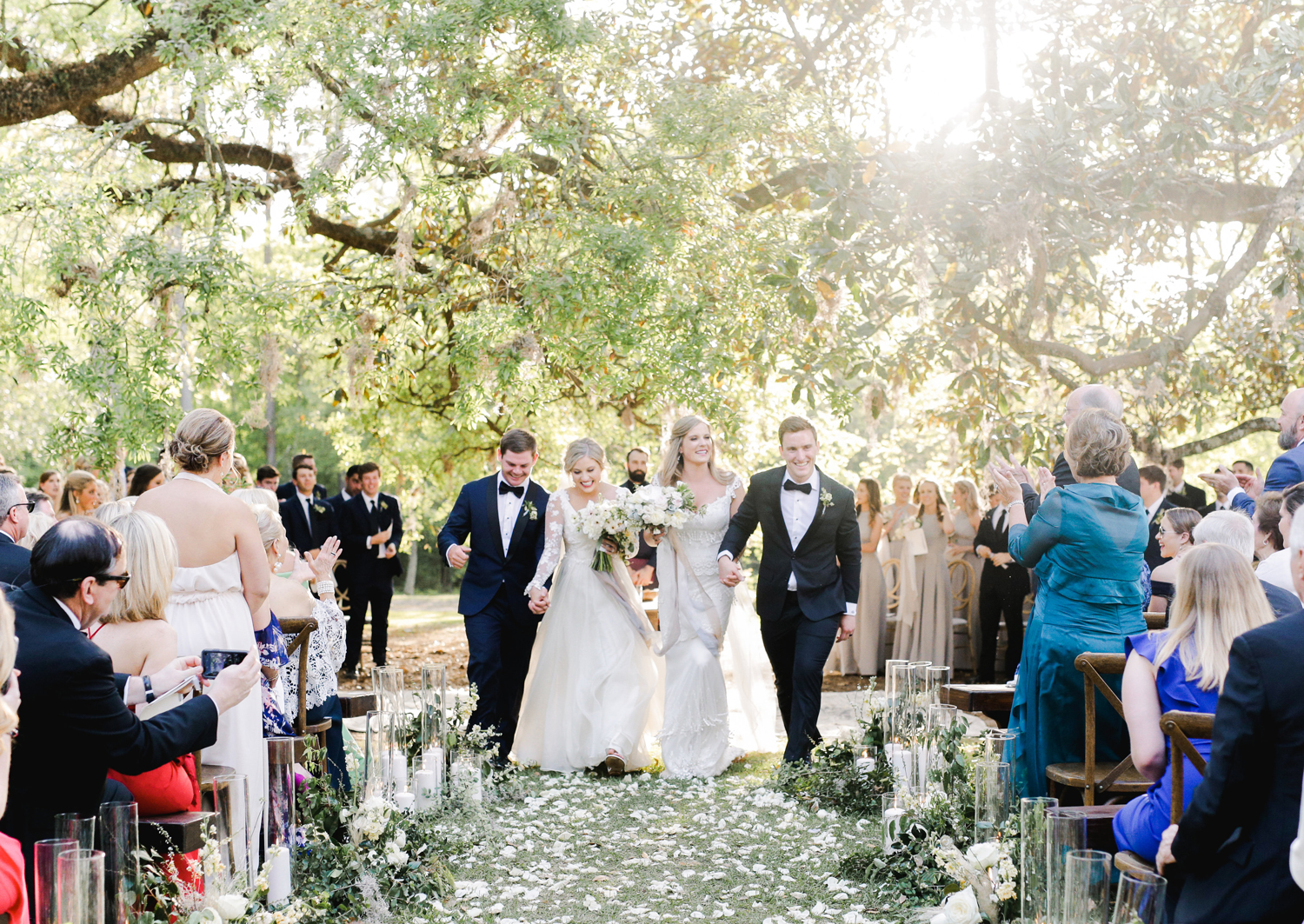 double wedding recessional couples holding hands walking down aisle