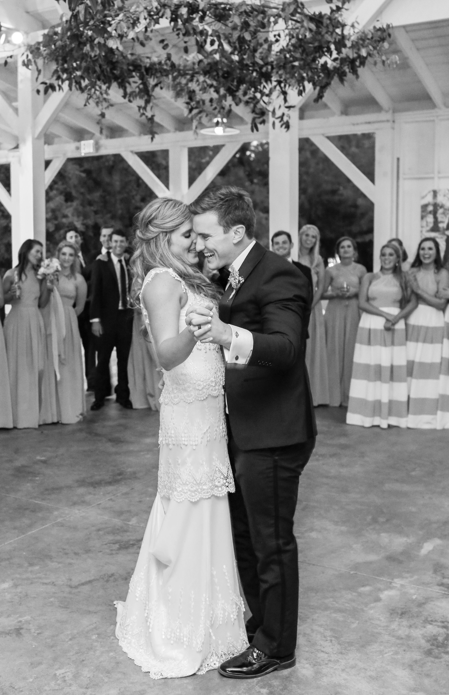 bride and groom sharing first dance watched by wedding party