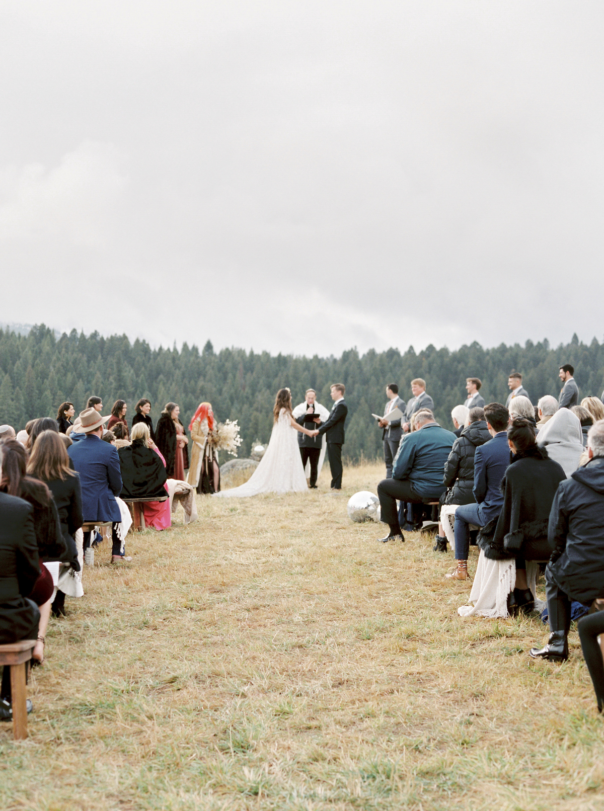 outdoor wedding ceremony with pine trees in background