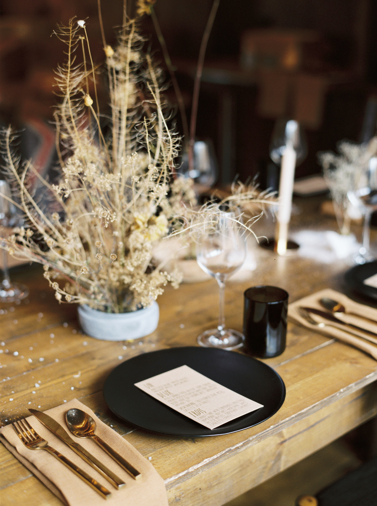 wedding reception table setup with black dishes and dried flowers