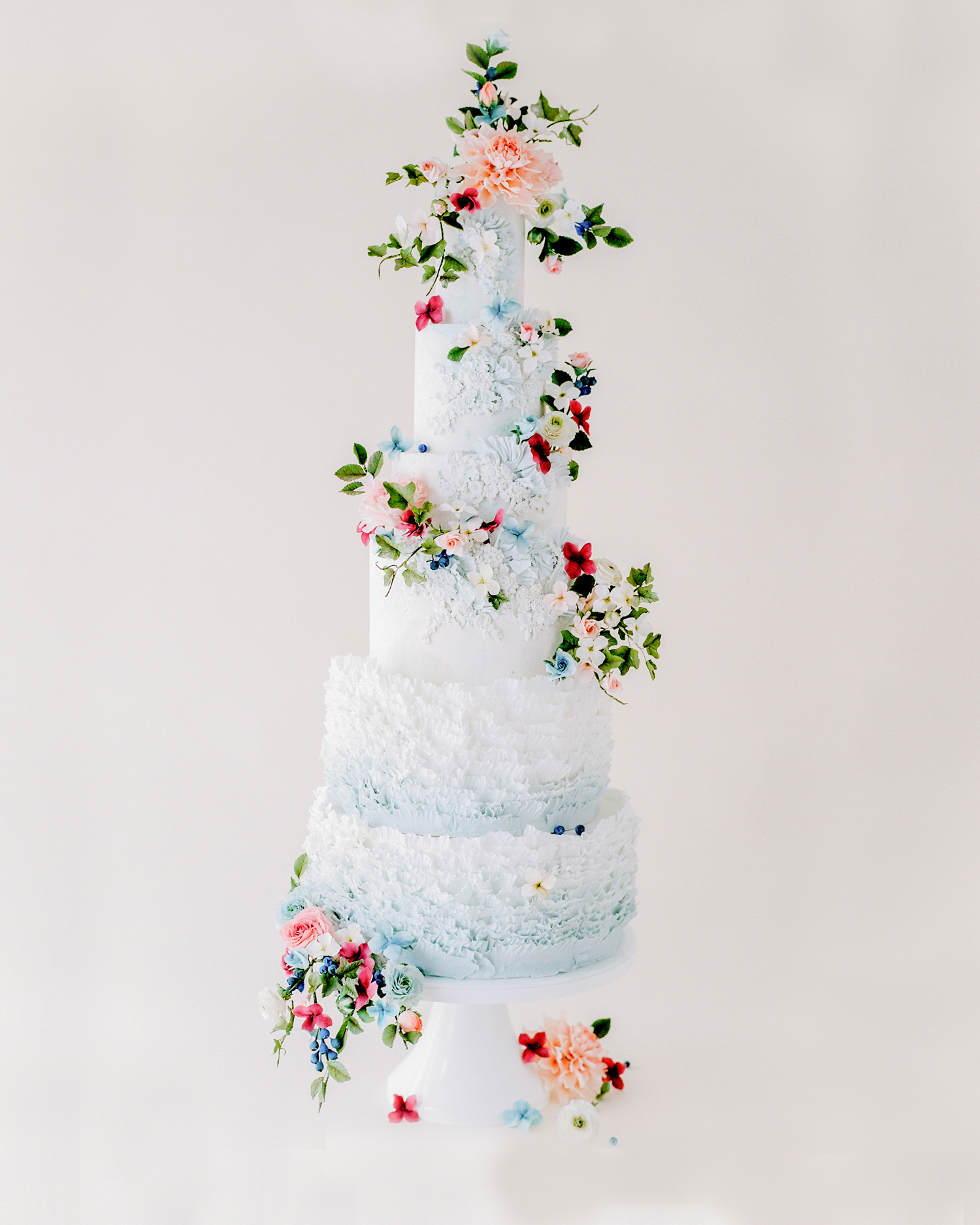 light blue wedding cake adorned with vibrant sugar flowers