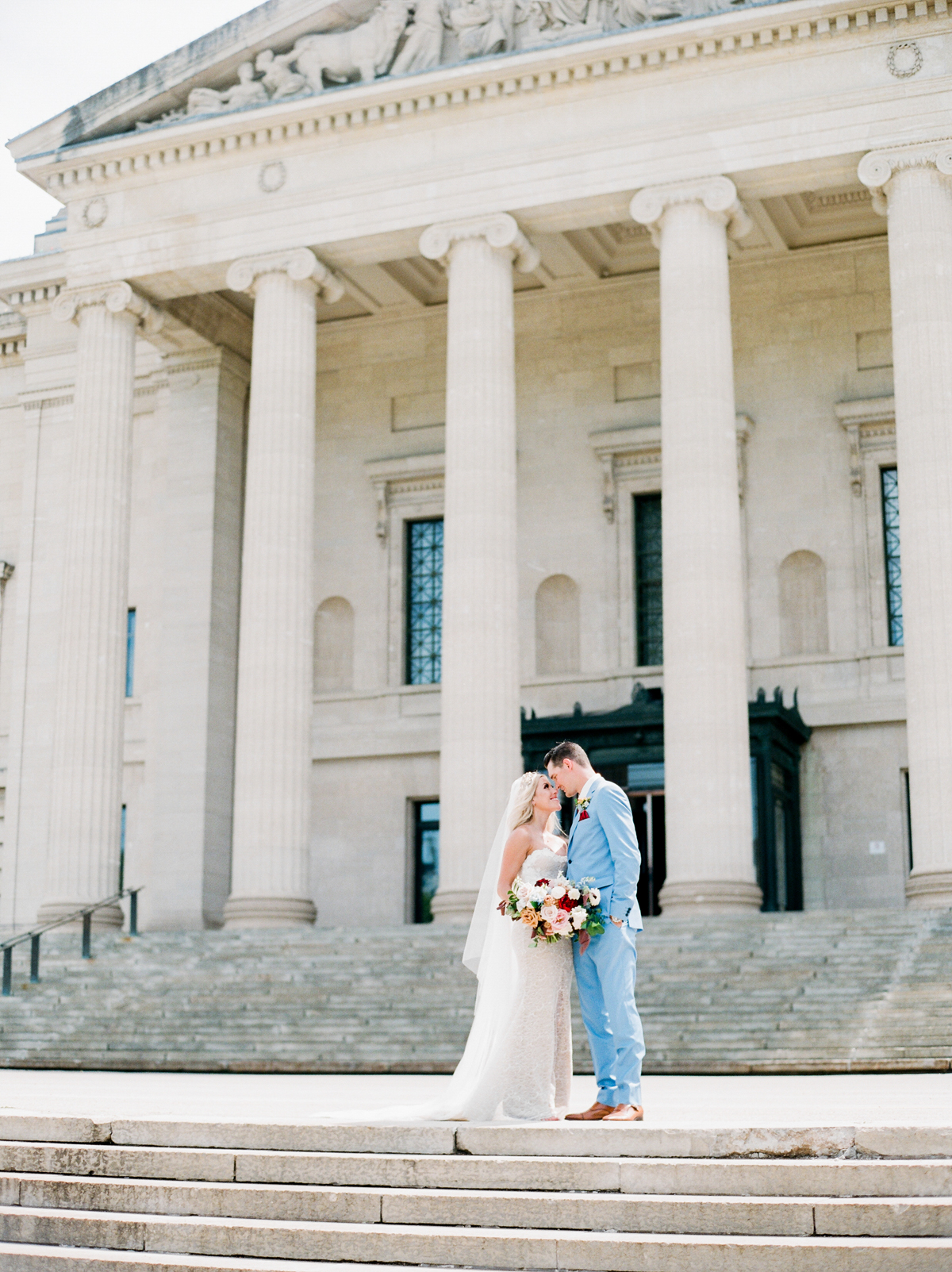 bride and groom looking at one another on steps of legislative building