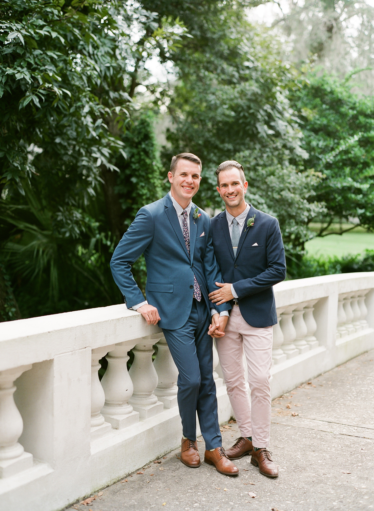 couple grooms pose holding hands