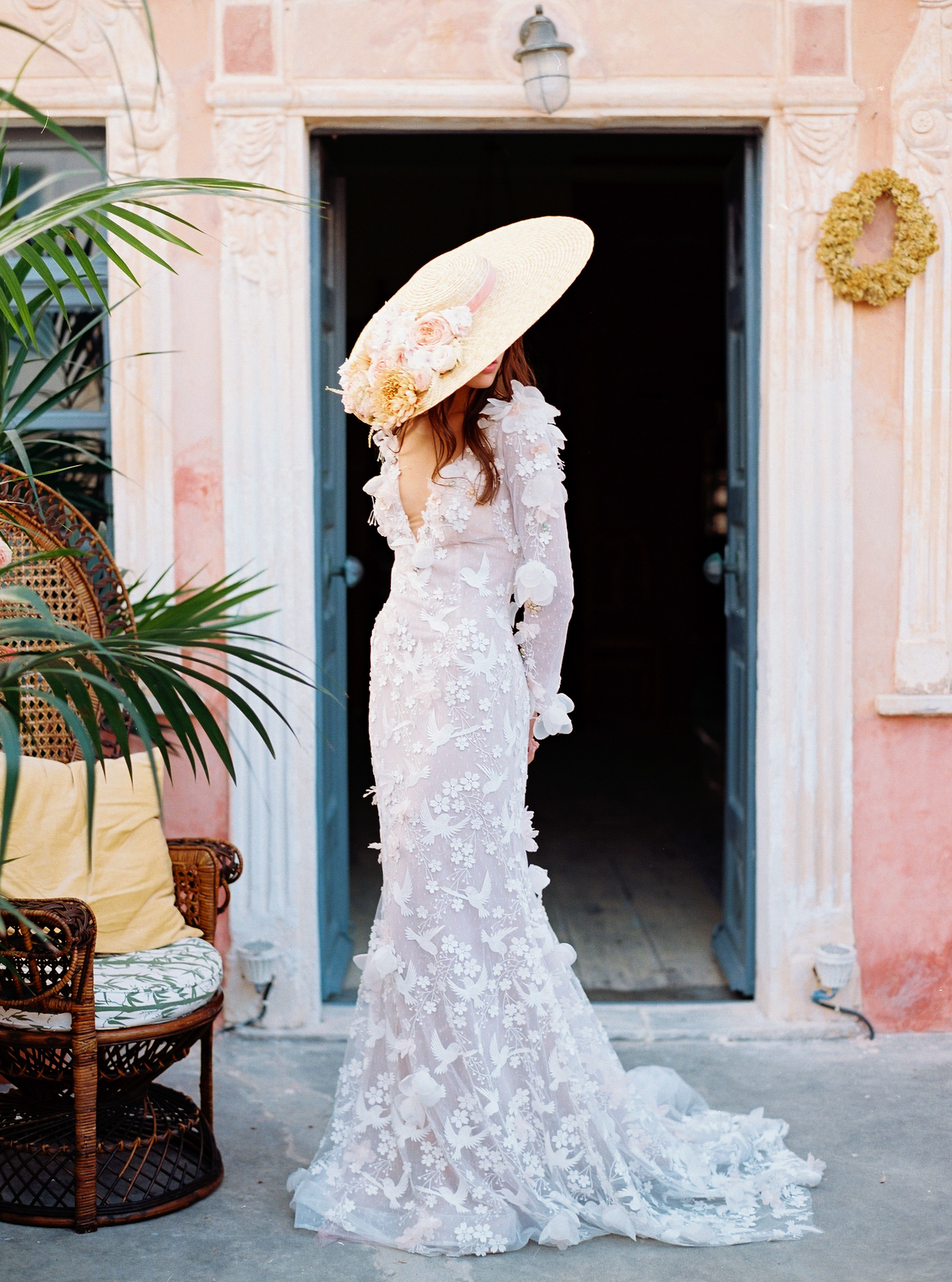 bride wearing large hat and floral dress