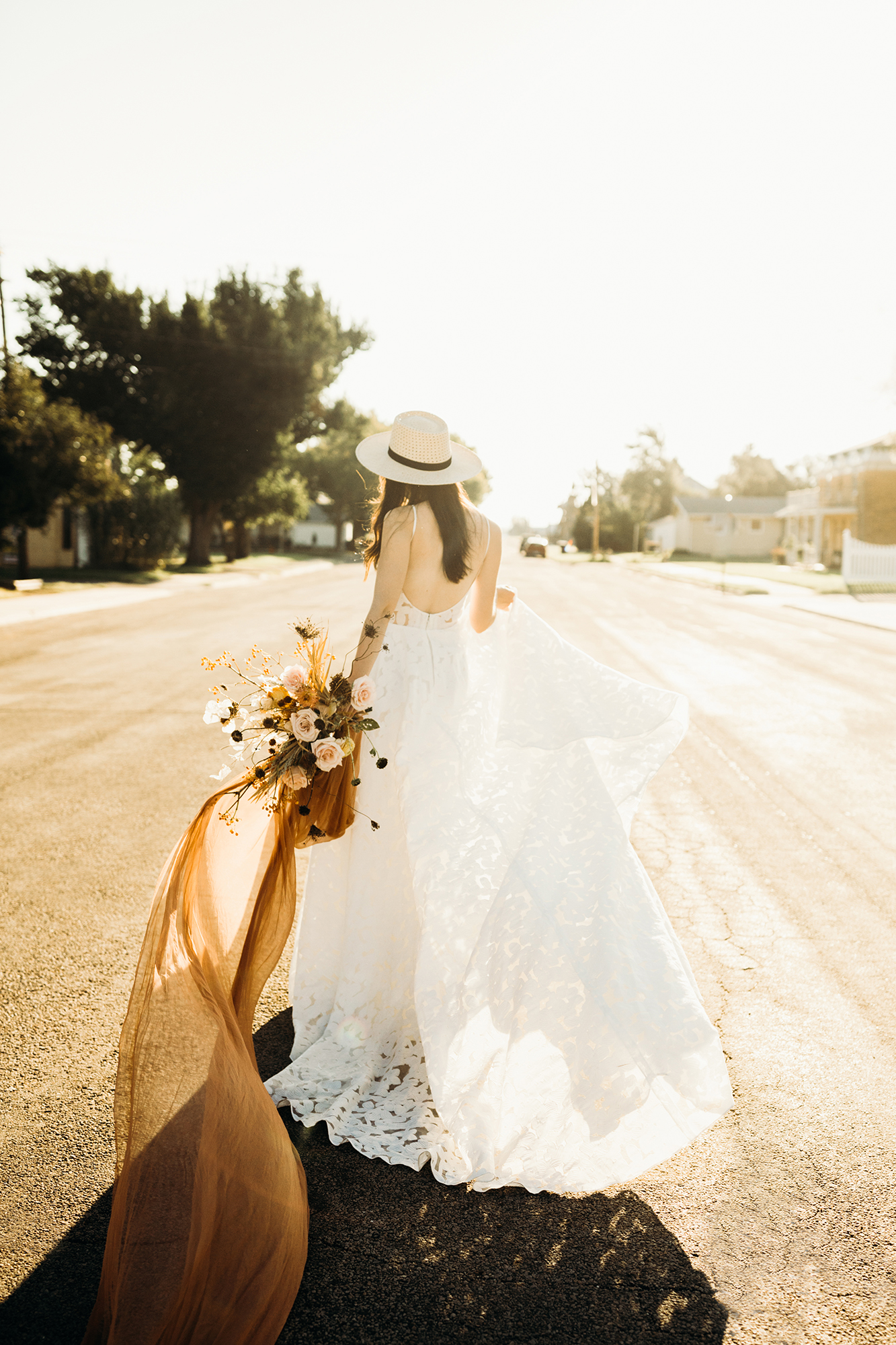 bride wearing off white hat with black ribbon