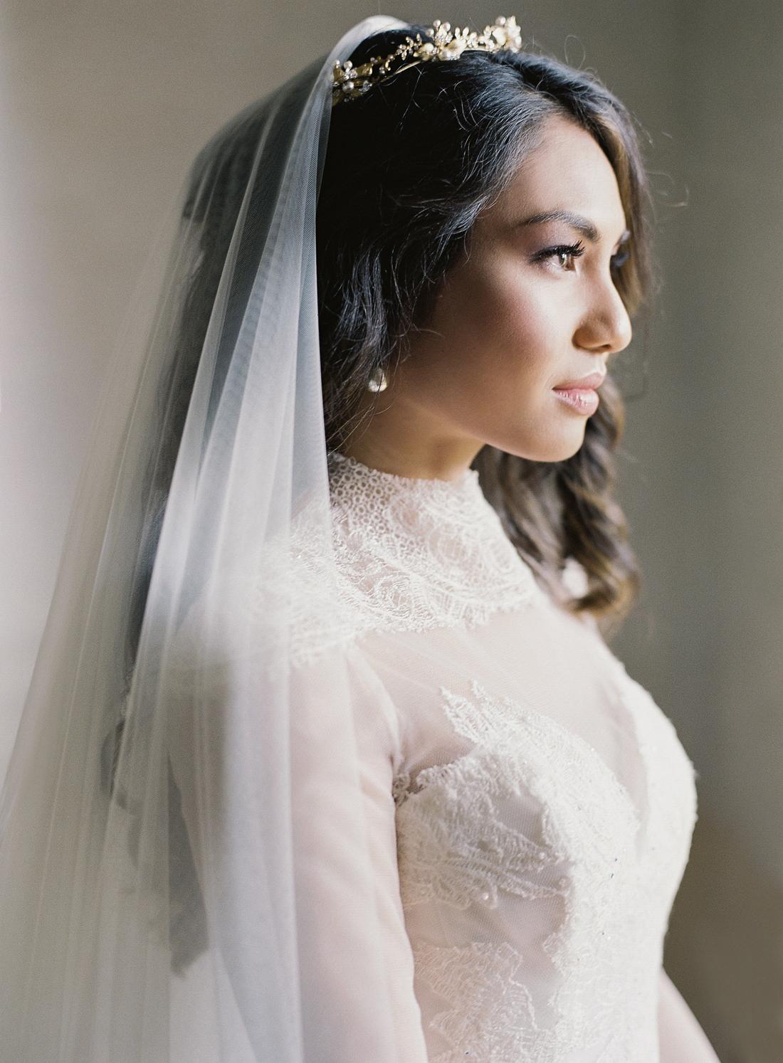 bride wearing veil, crown, and vintage pearl earrings