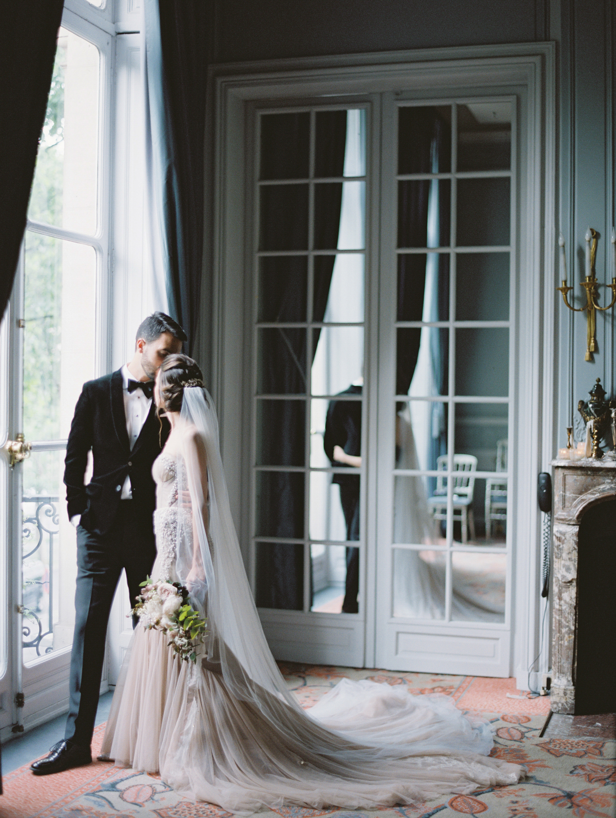 bride and groom kissing near window in parisian salon