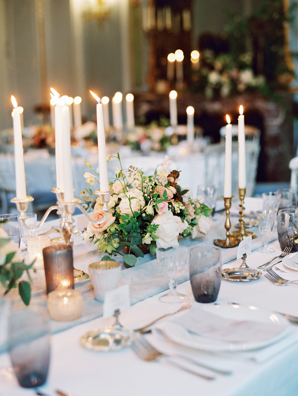 wedding reception table setting decorated with candle sticks and roses