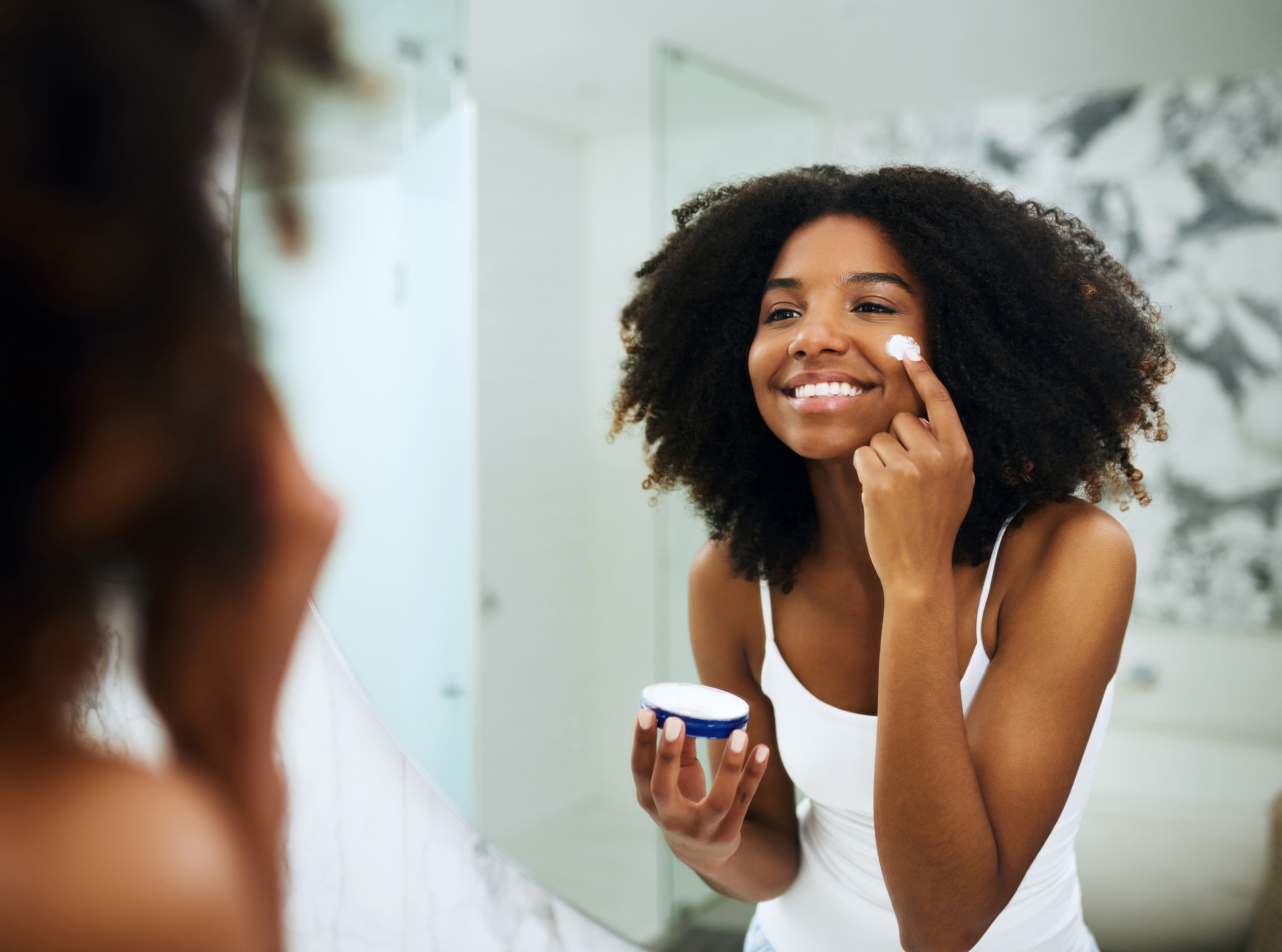 Young Woman Applying Skincare Products