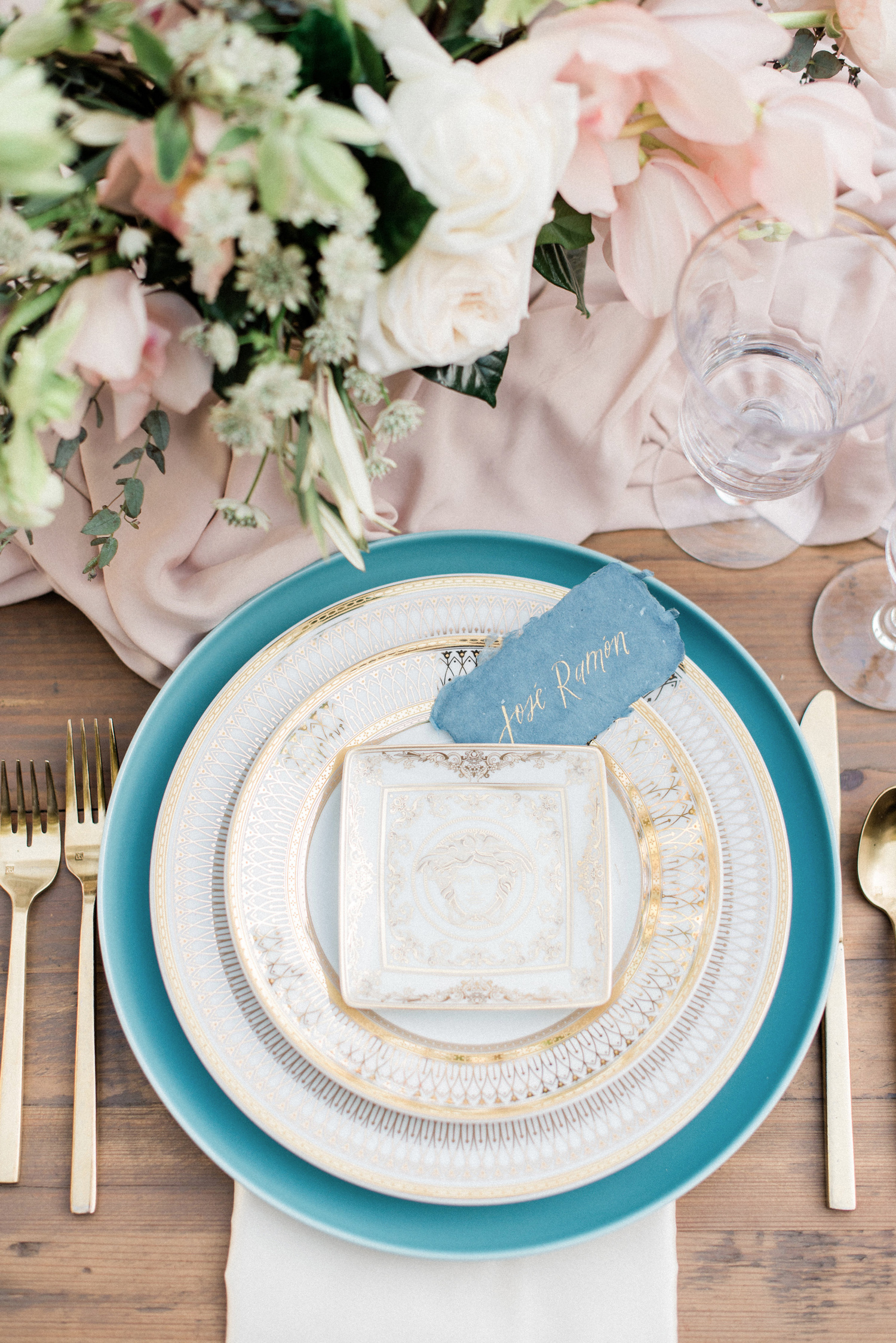 white plates with gold and teal accent designs with gold silverware