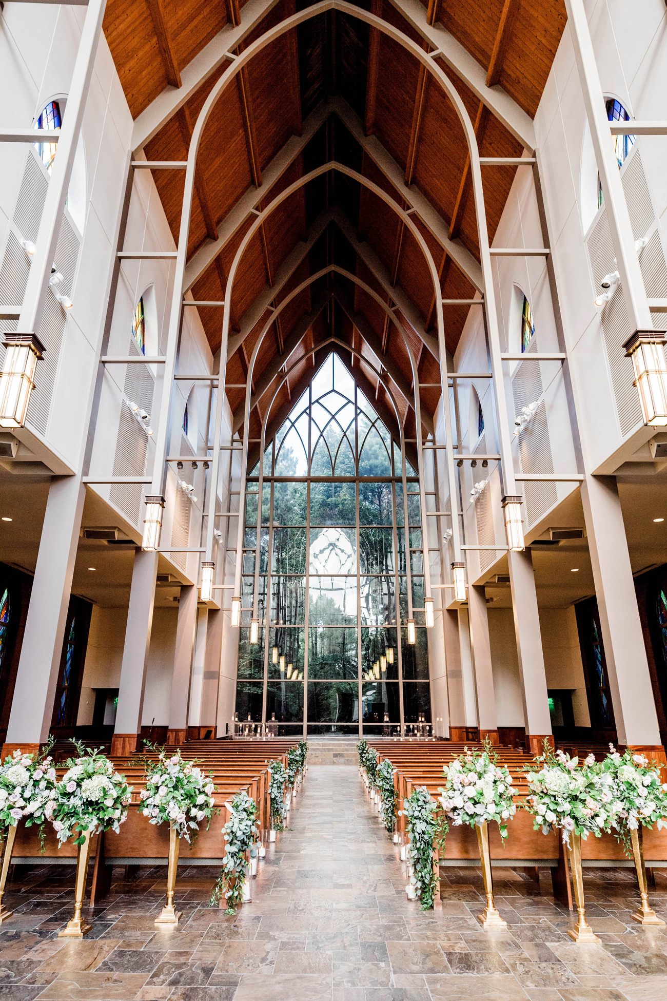 tall floral arrangements and candles lined wedding ceremony aisle