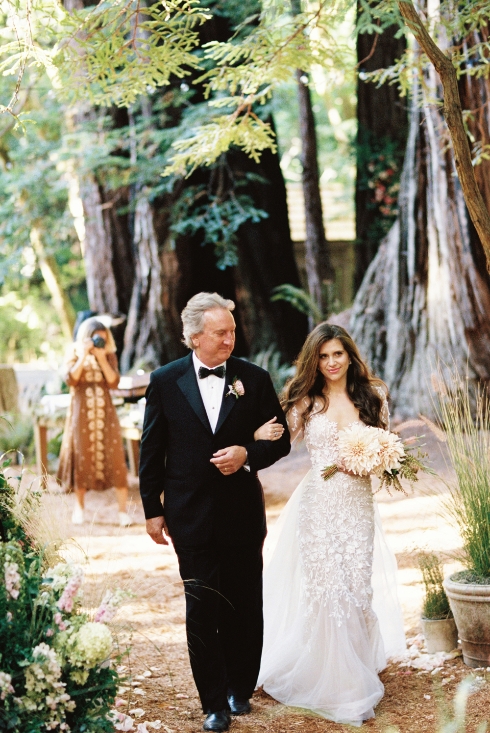 father of the bride walking bride down outdoor forest wedding aisle