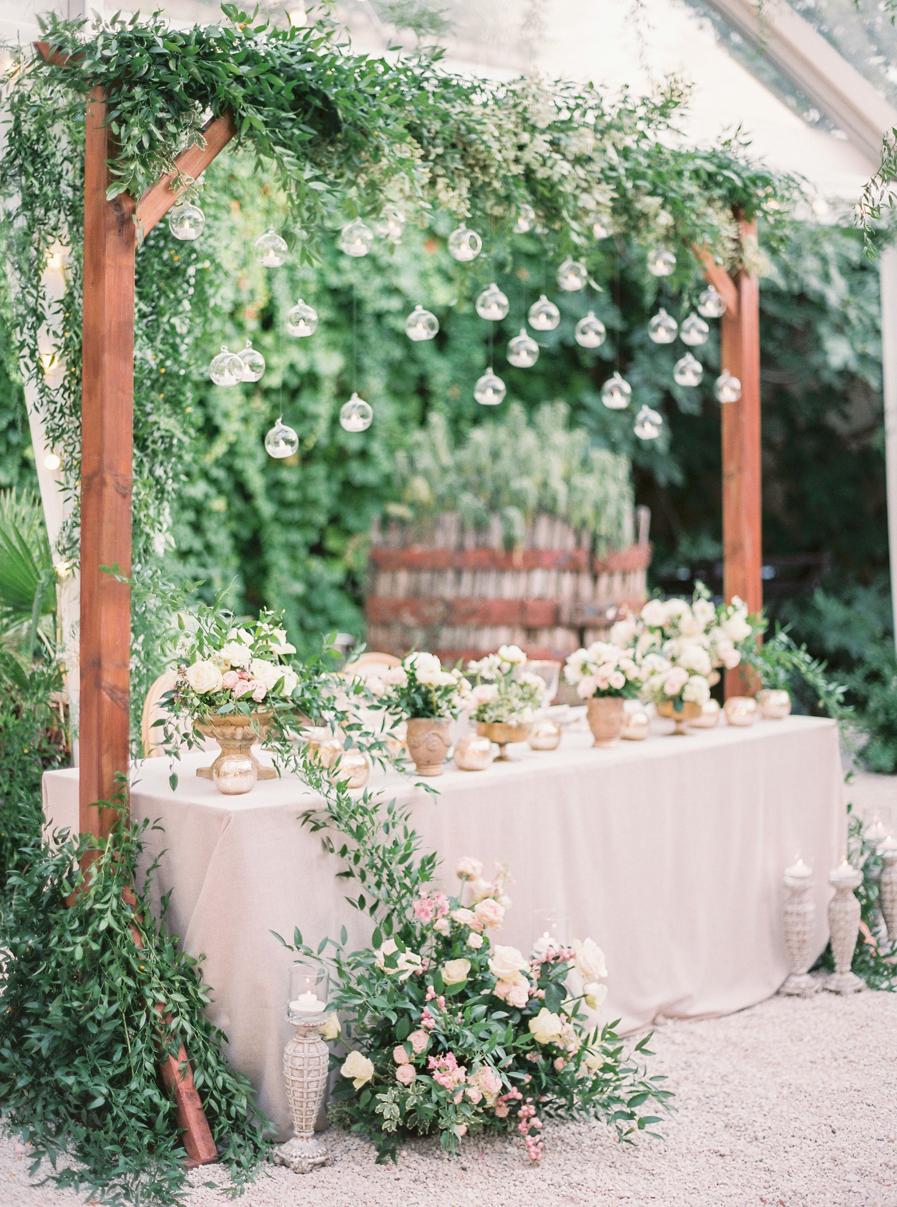 head table installation with florals greenery and tea lights
