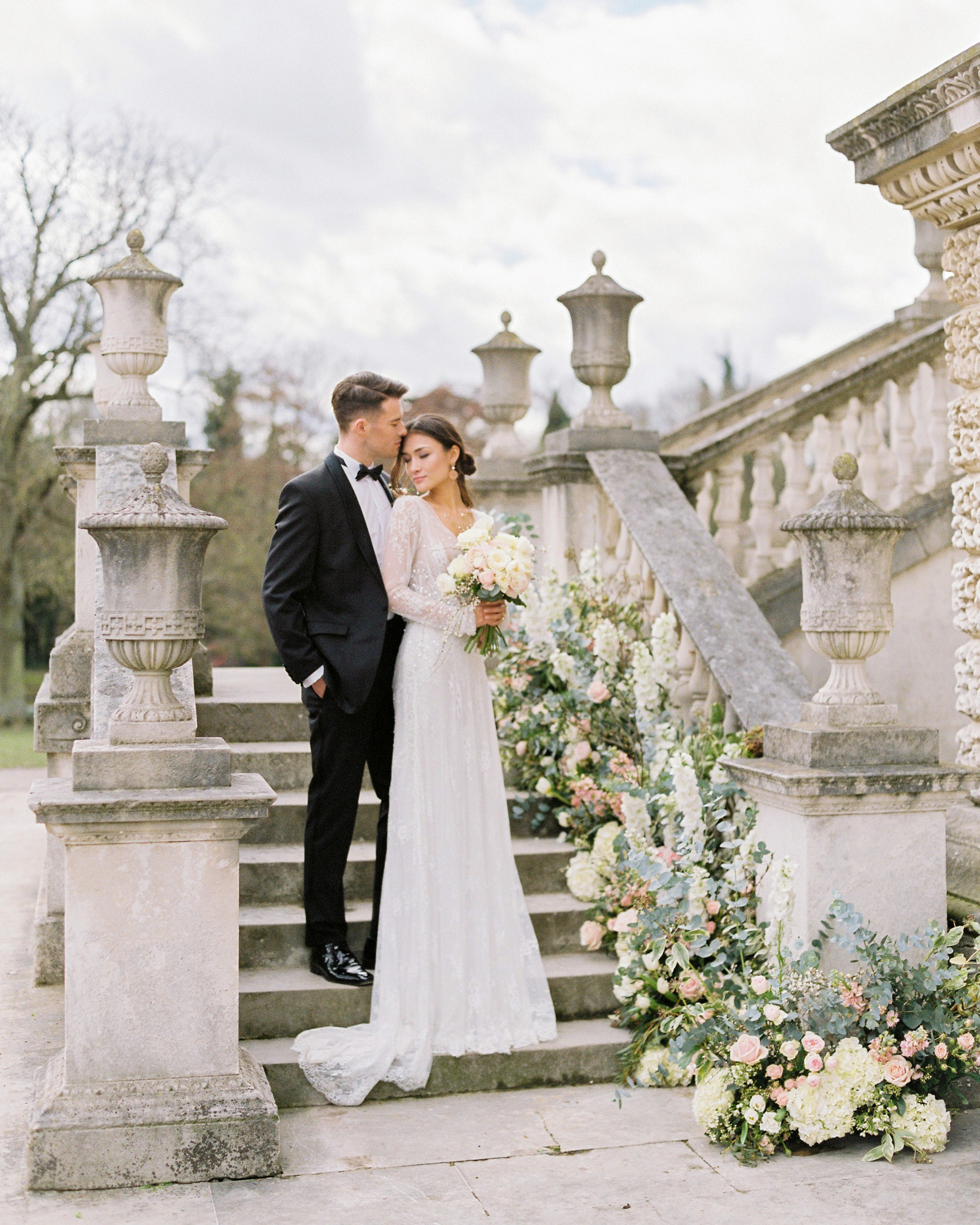bride groom pose on decorated floral staircase