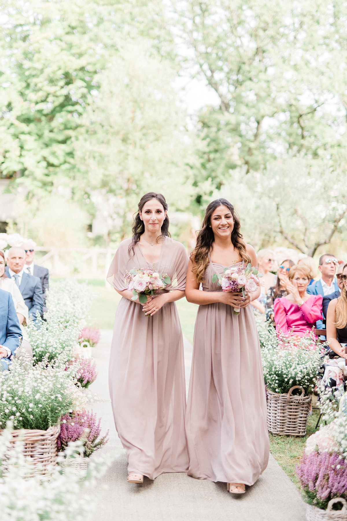 two bridesmaids walking down wedding aisle wearing mauve dresses