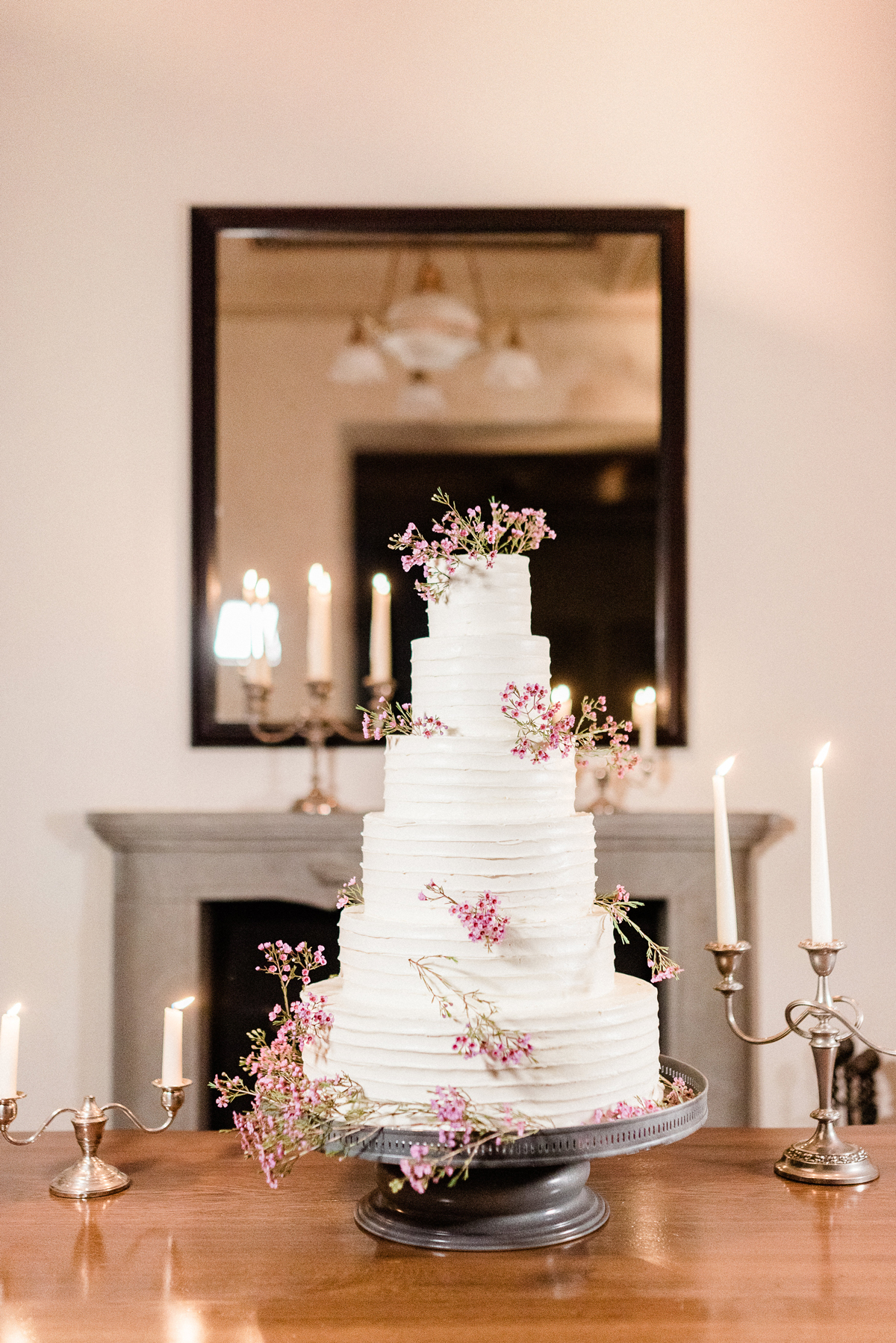six tiered white frosted wedding cake with pink floral decor accents