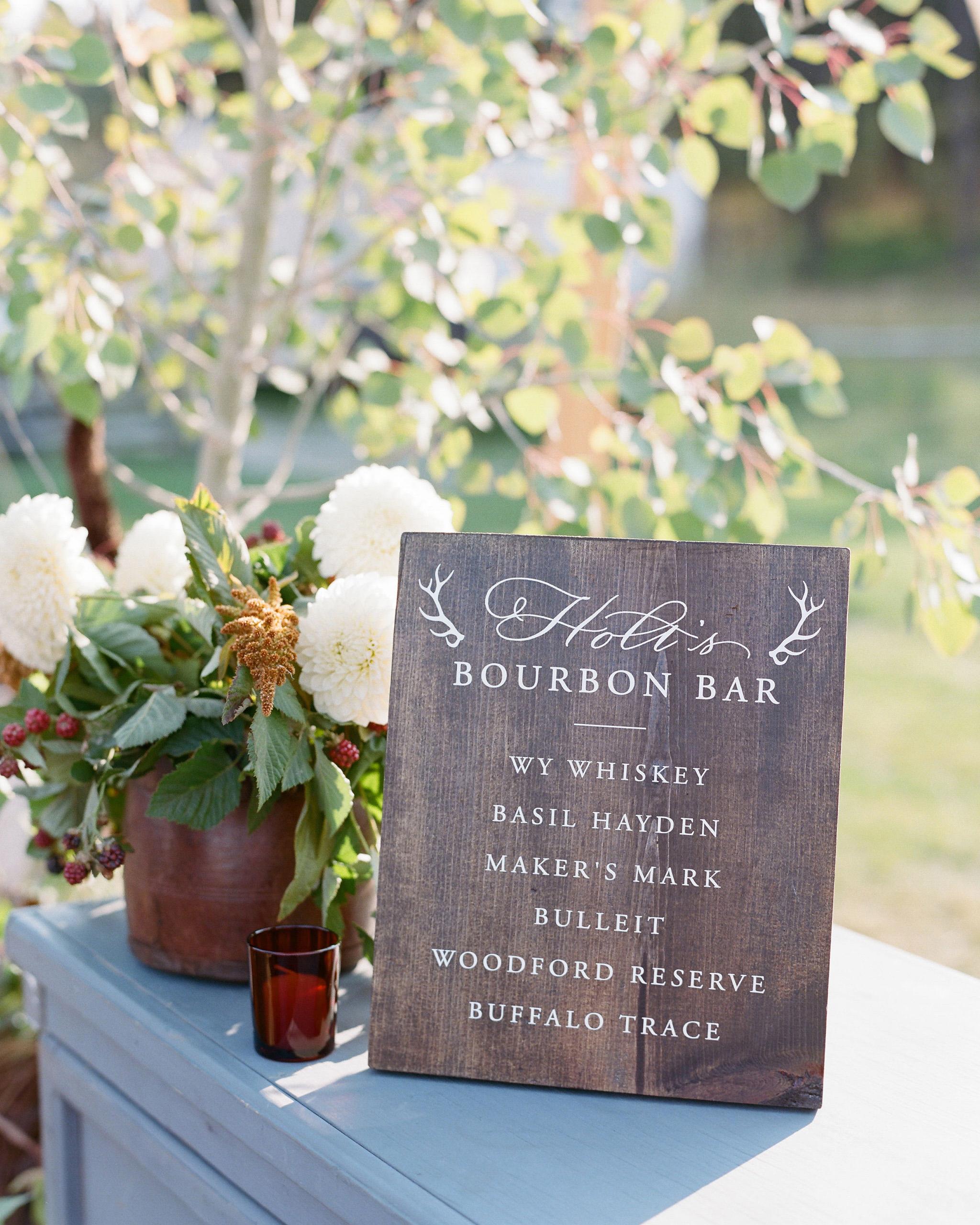 bourbon bar wood sign menu next to white flowers