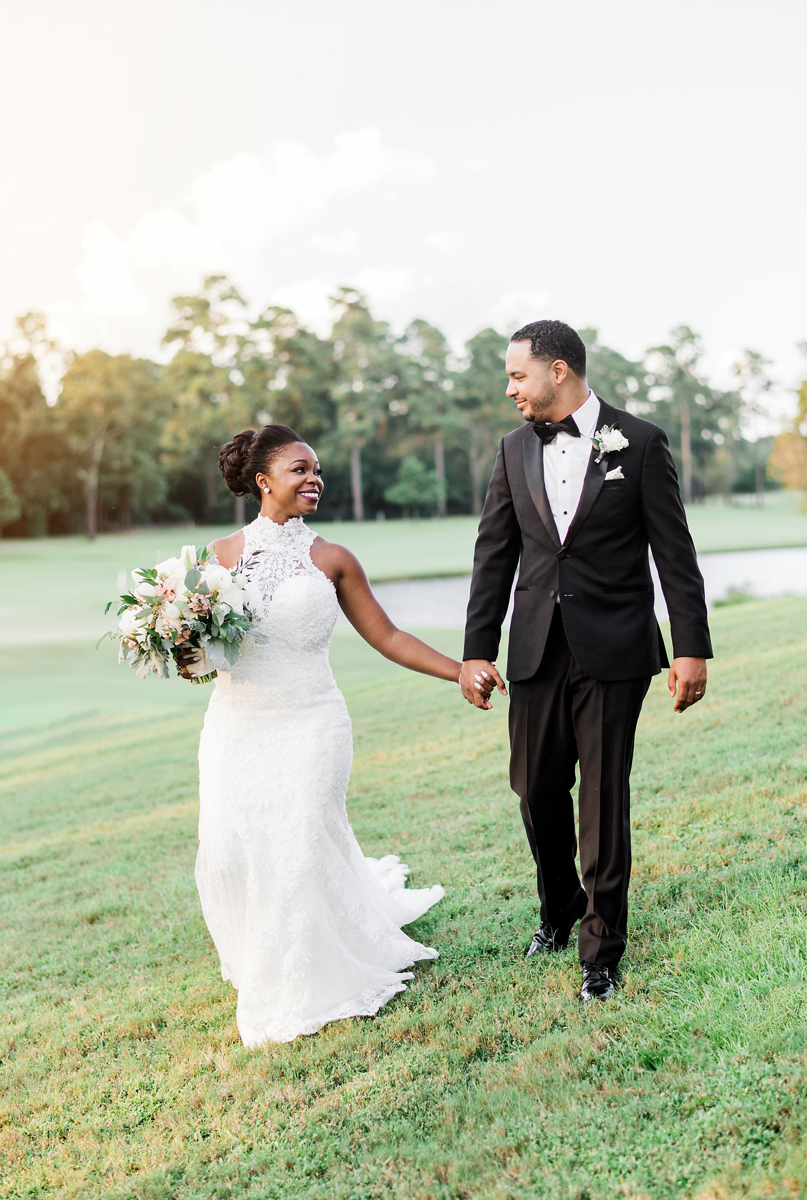 bride and groom smile holding hands on a grassy lawn outdoors