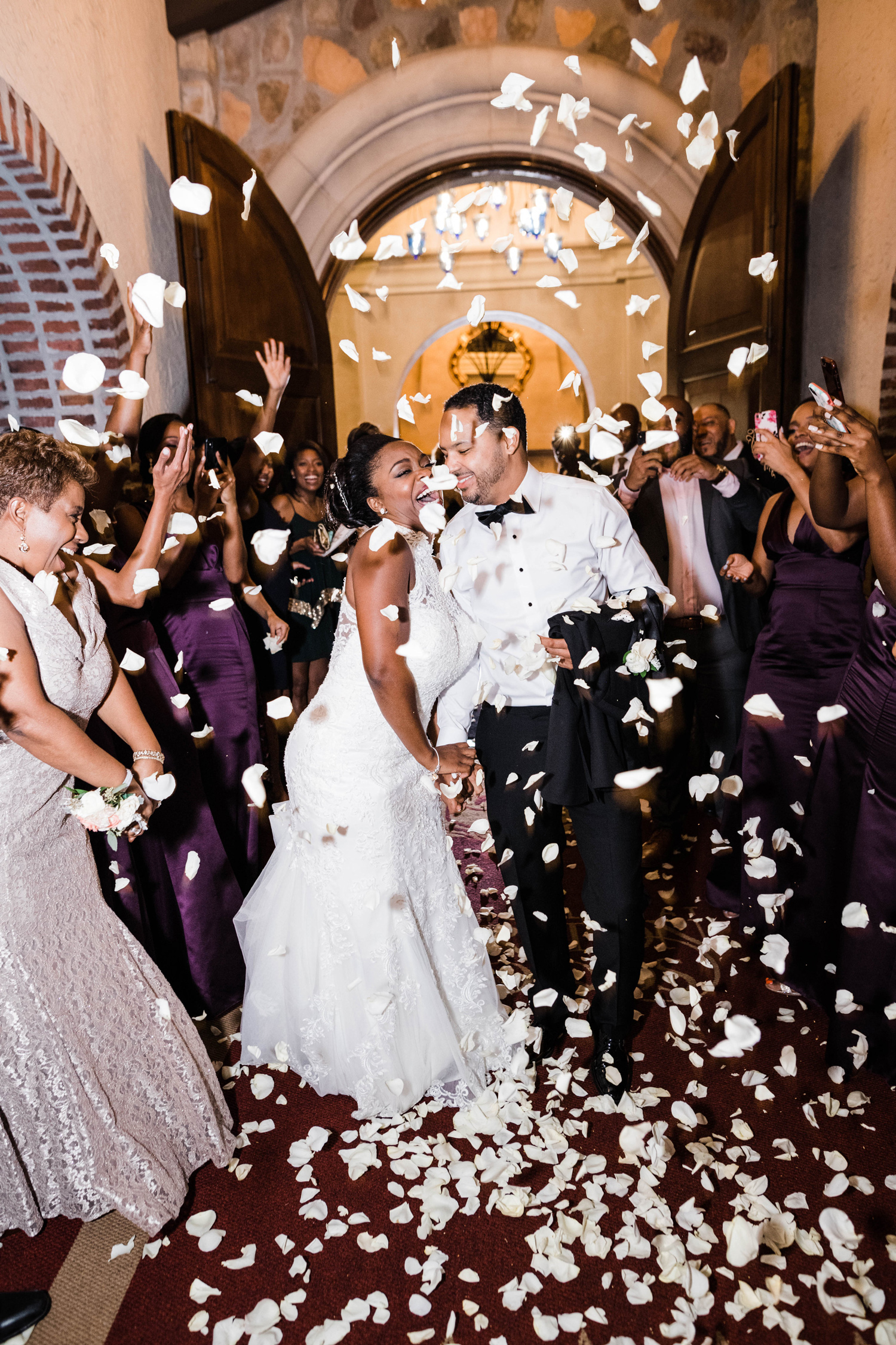 bride and groom showered with flower petals by guests