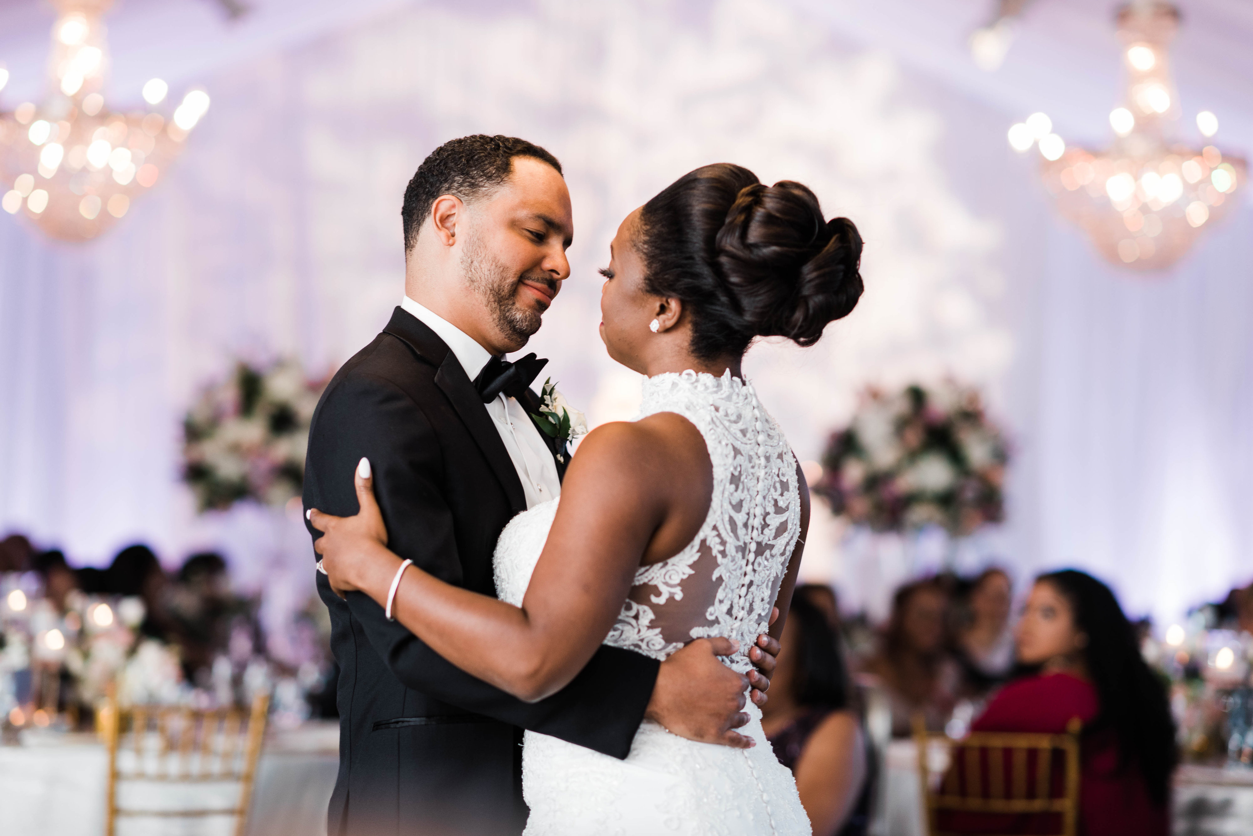 bride and groom hold each other during first dance at wedding reception