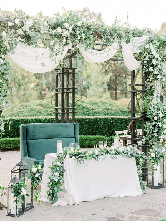 sweetheart table greenery arch and outdoor table