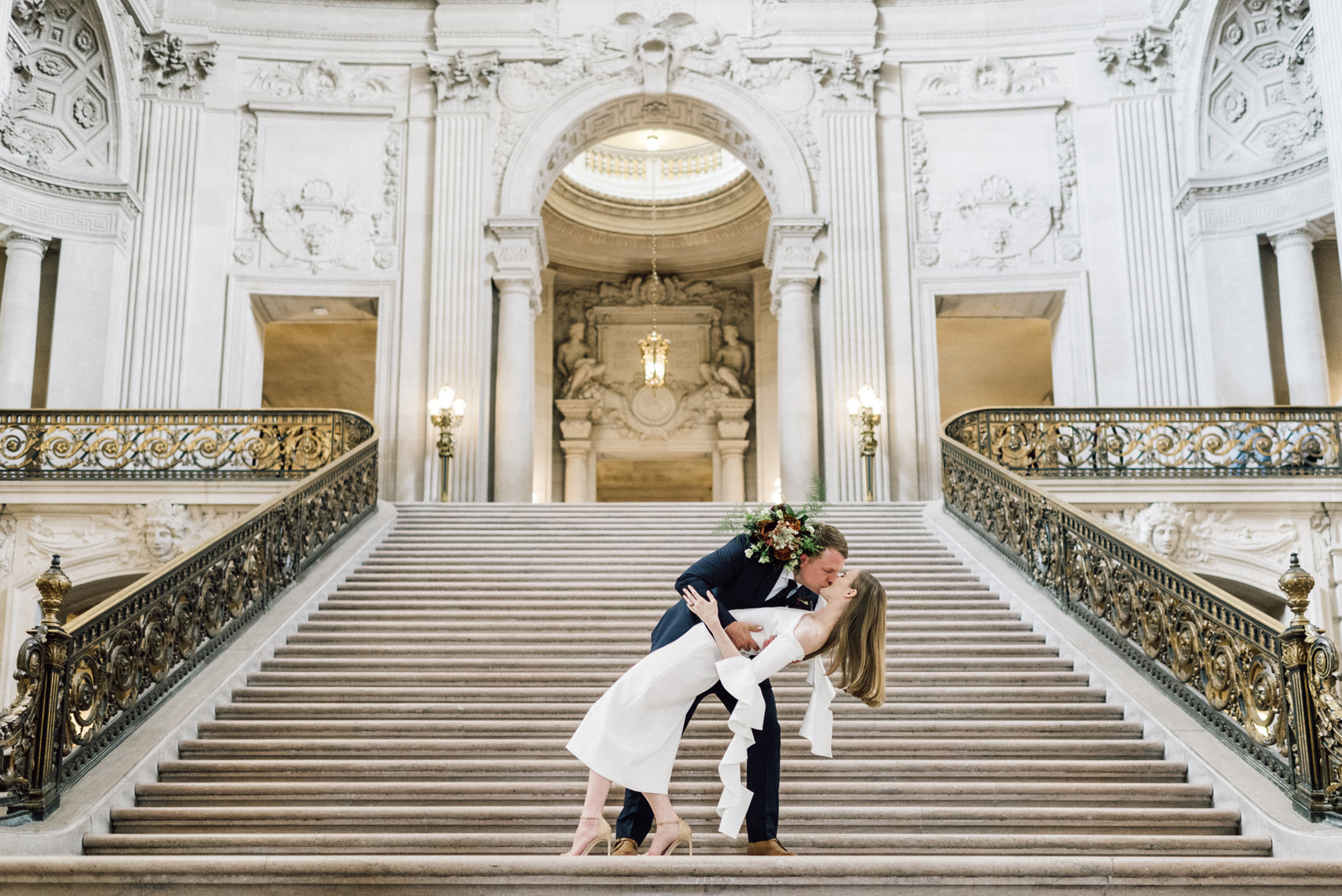 groom dips bride on city hall steps