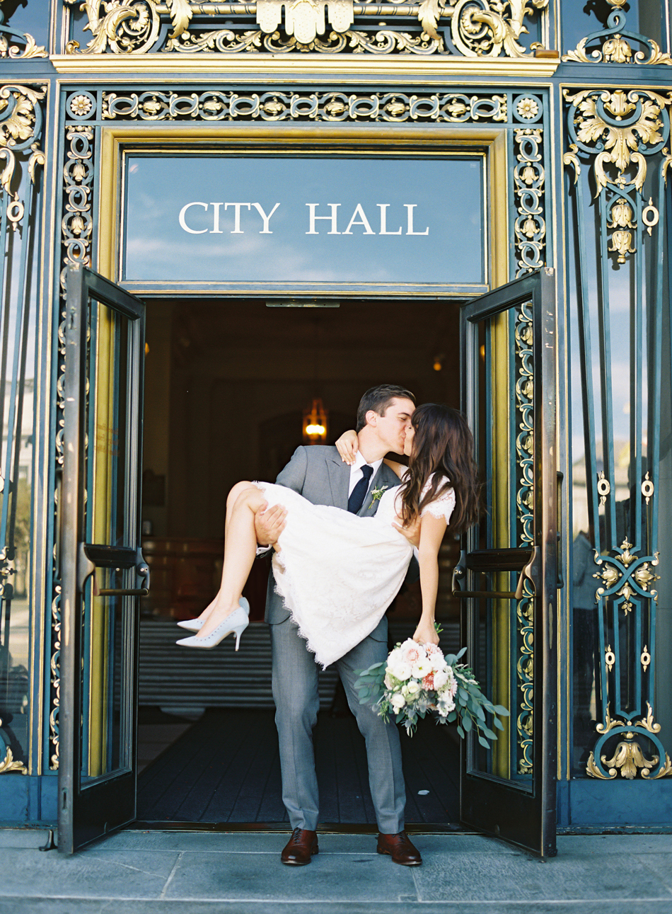 groom carries bride out of city hall after wedding ceremony