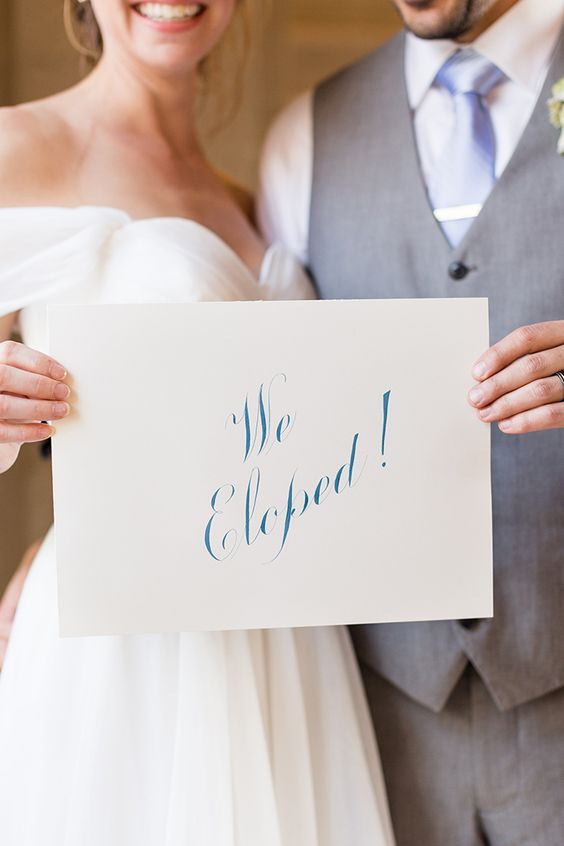 "bride and groom holding white wedding sign with blue writing ""we eloped"""