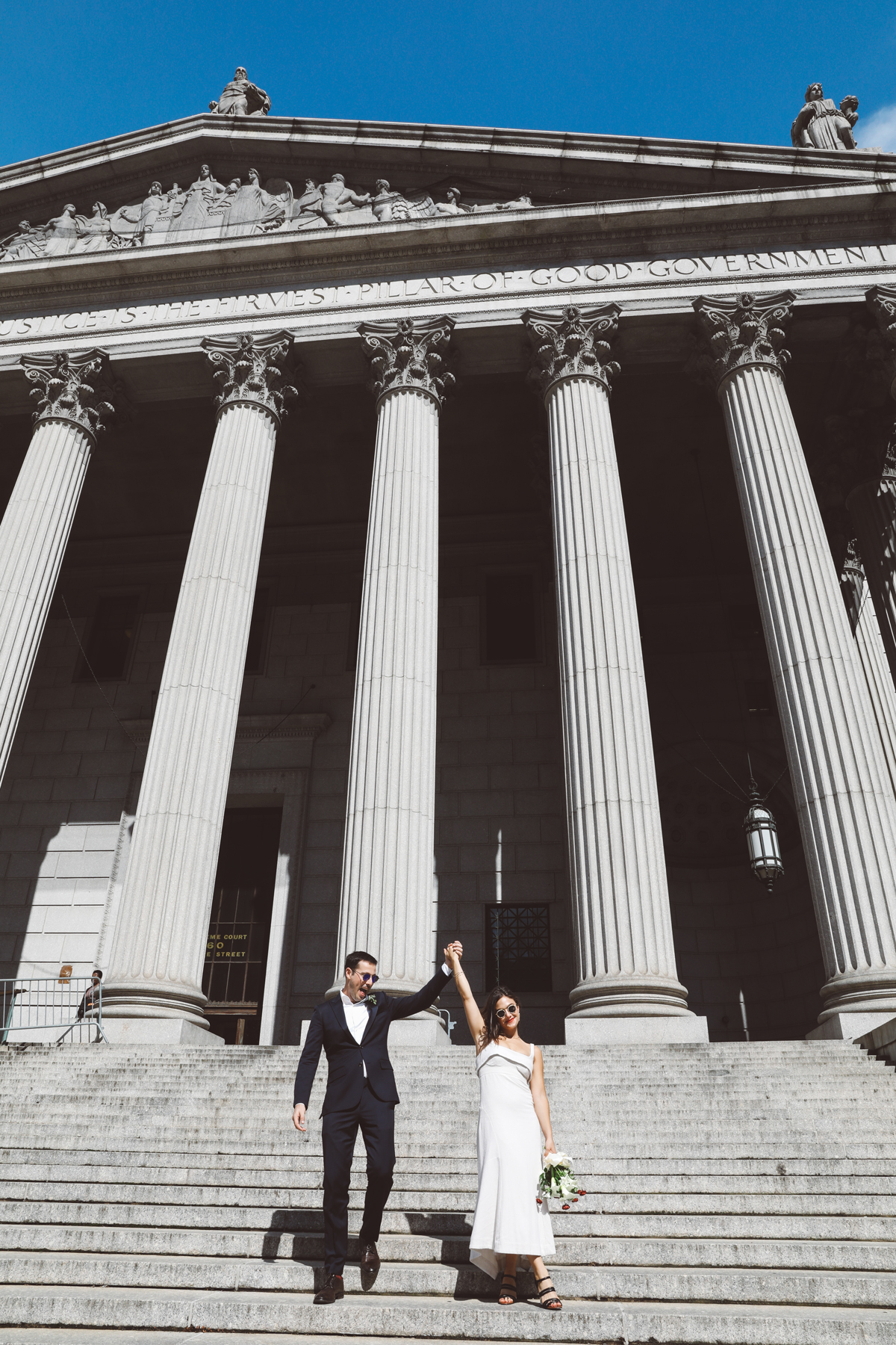 bride and groom holding hands walking down city hall steps after wedding ceremony
